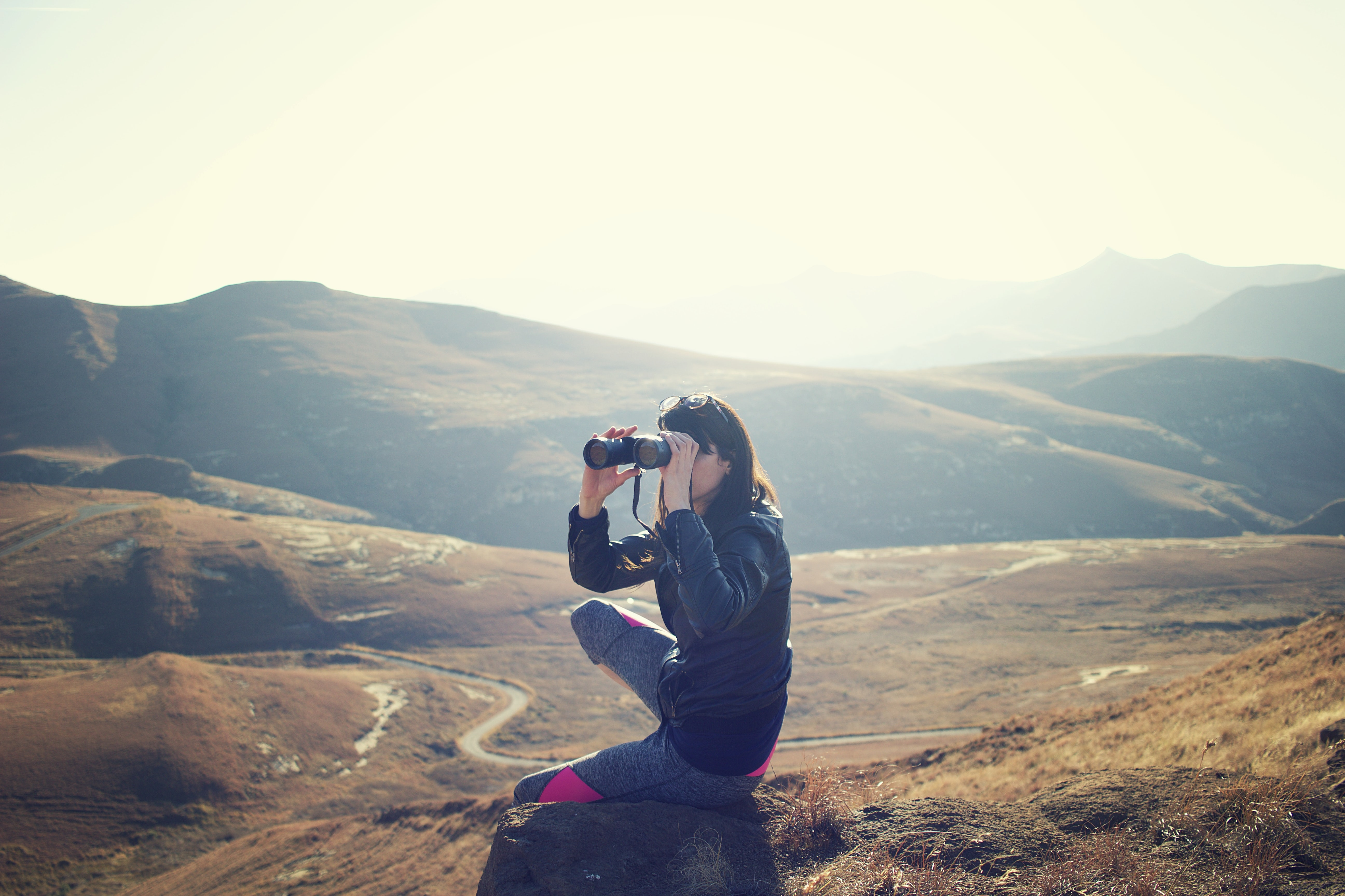 woman wearing black jacket sitting on gray rock and using binoculrs