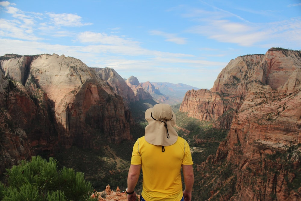 man wearing yellow shirt standing on edge of cliff facing rock formations
