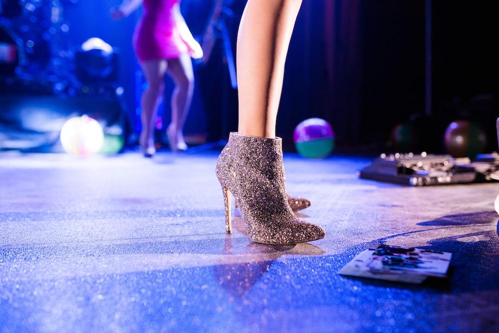woman wearing gray booties dancing