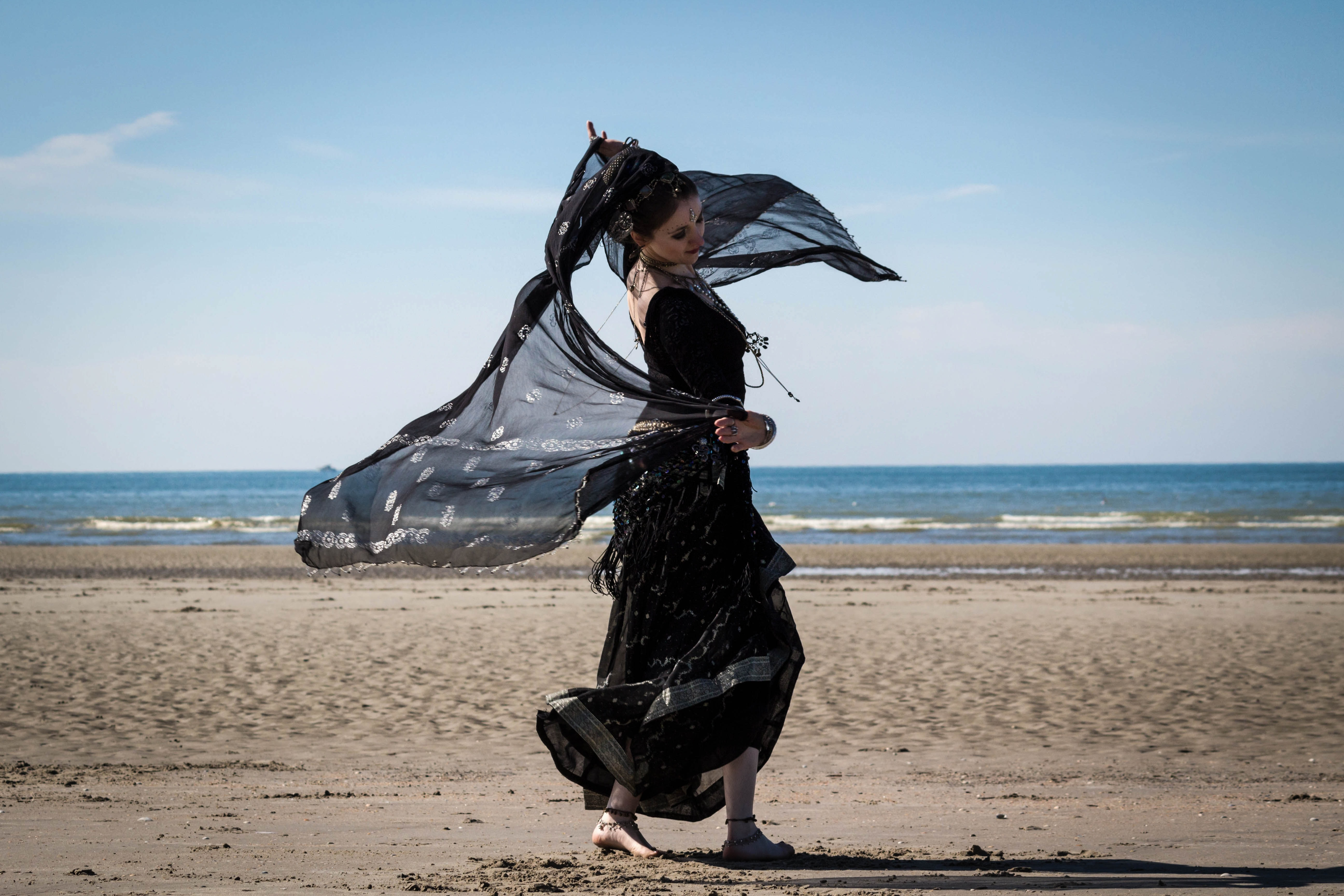 Woman in black dancing on the sand beach at De Panne