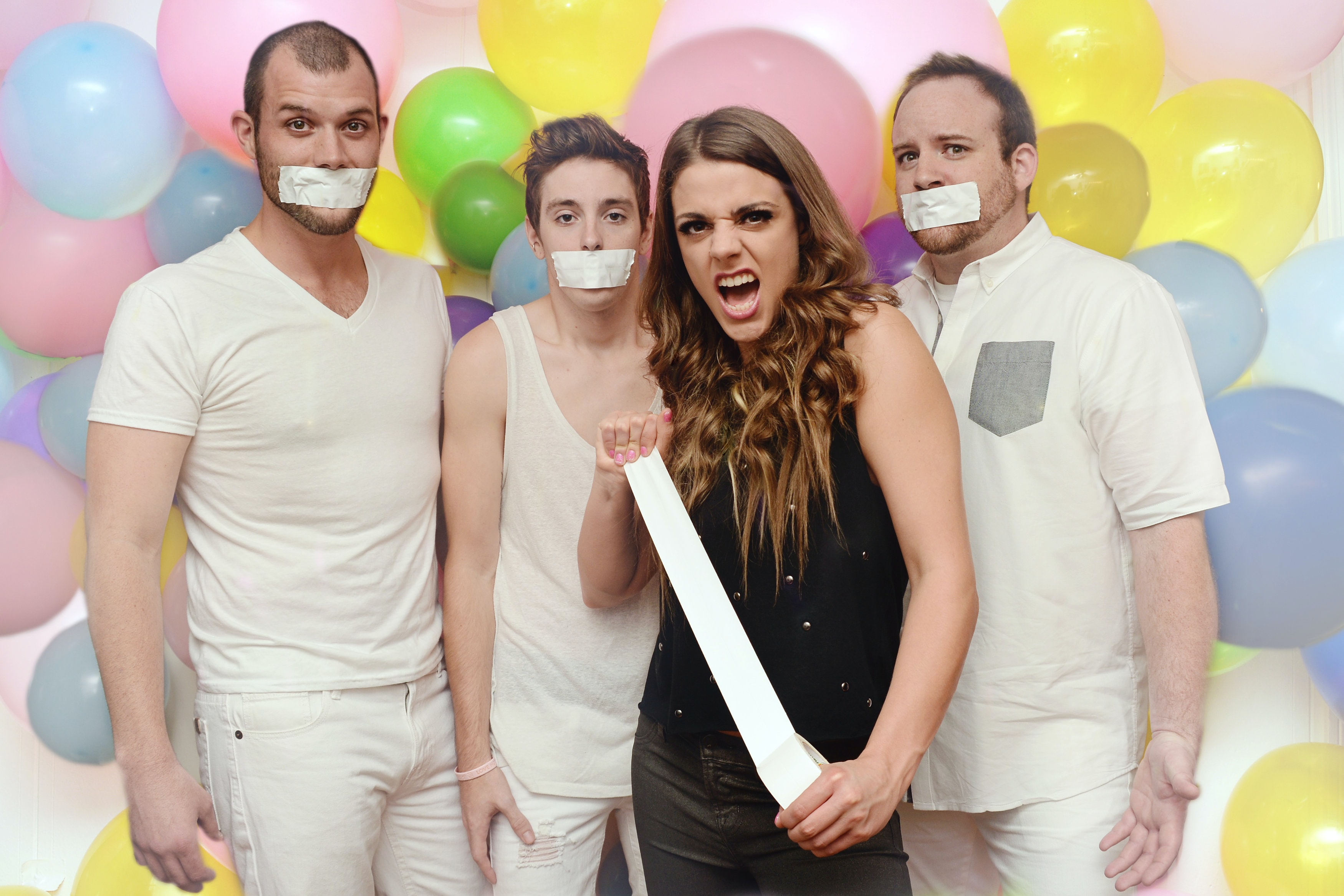 A woman holding a tape standing in front of three men in white with tape covered mouths and balloons behind them