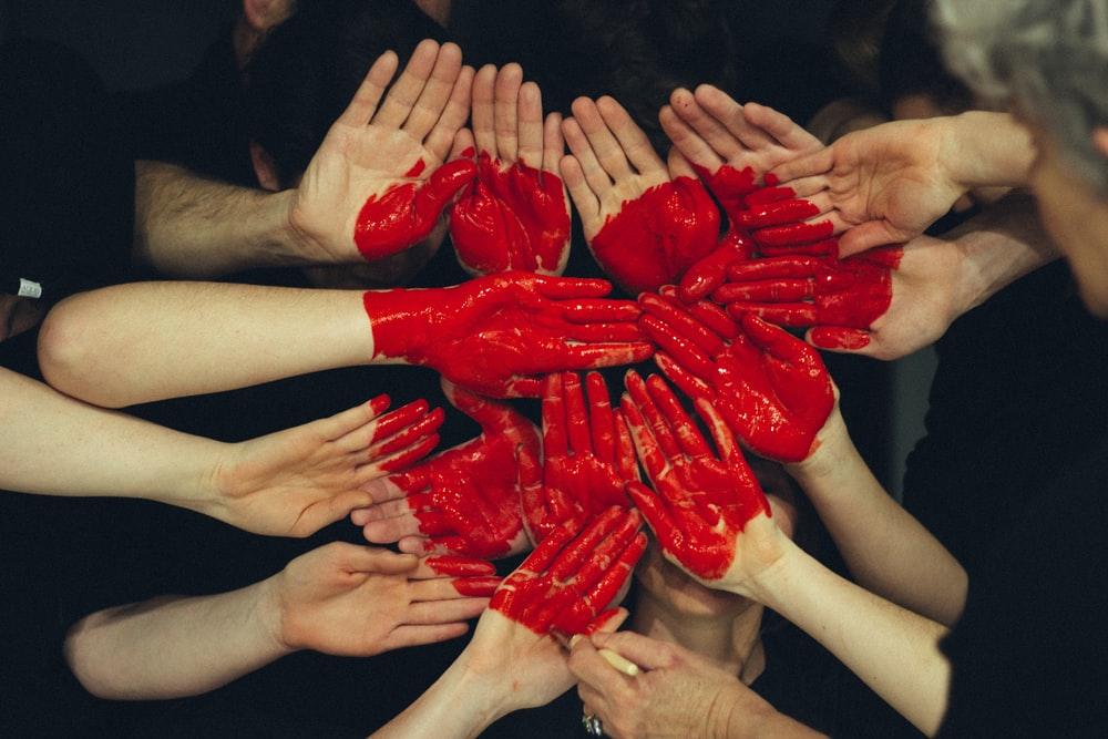 Many people's hands are painted red to form together a large red heart
