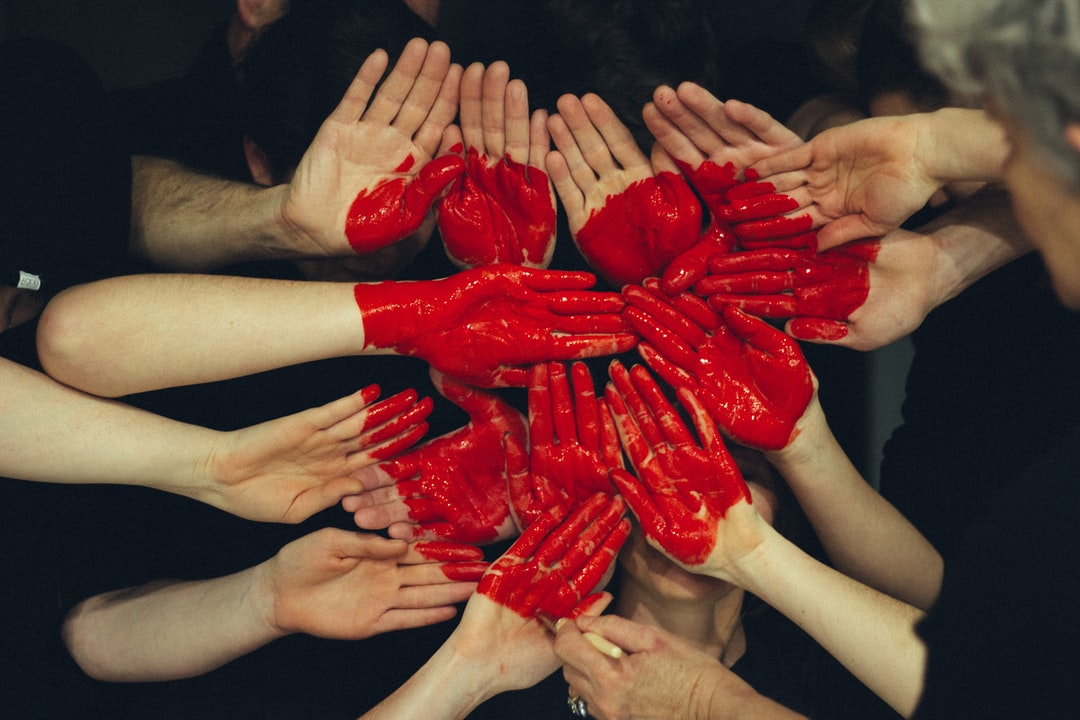 Hands with red paint shaping a heart