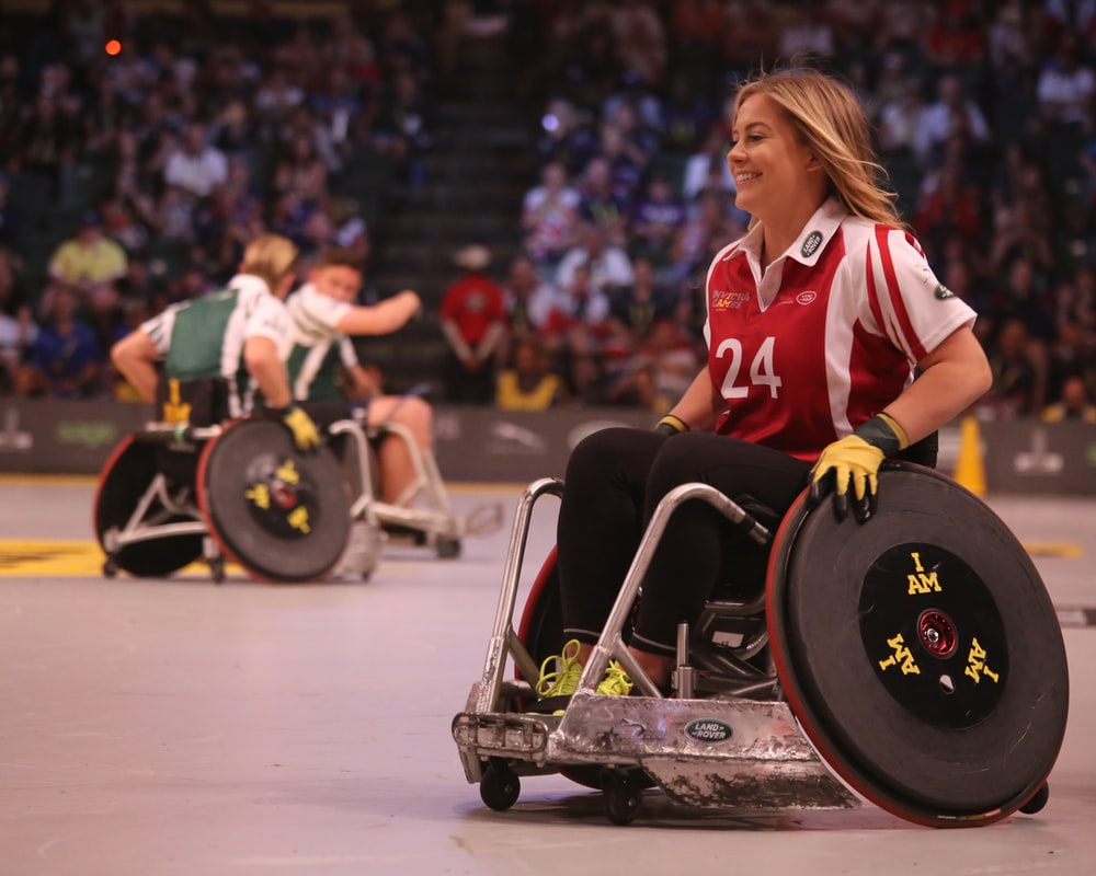 focus photo of woman in red and white polo shirt with black pants in ice wheelchair