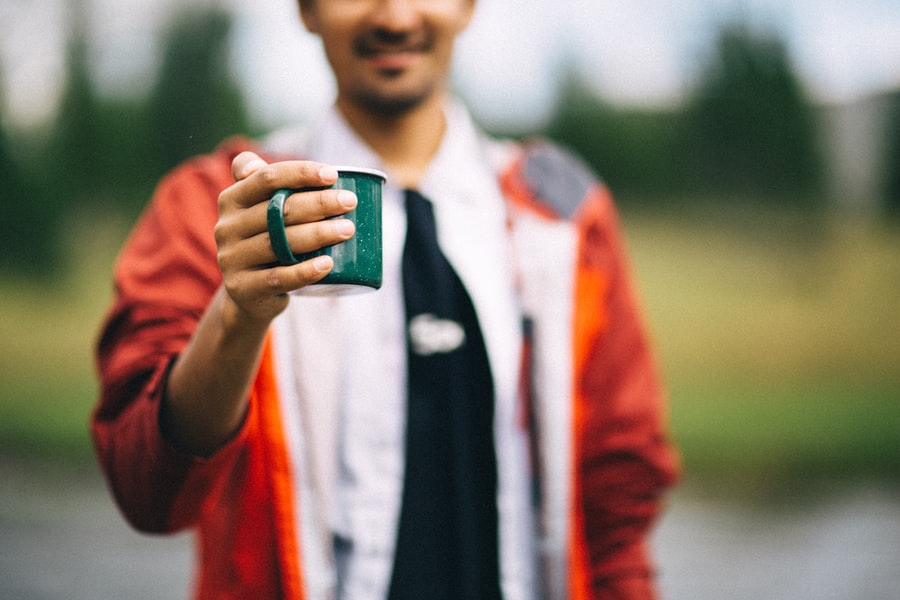 A man in a red jacket (out of focus) holds a small green mug towards the camera.