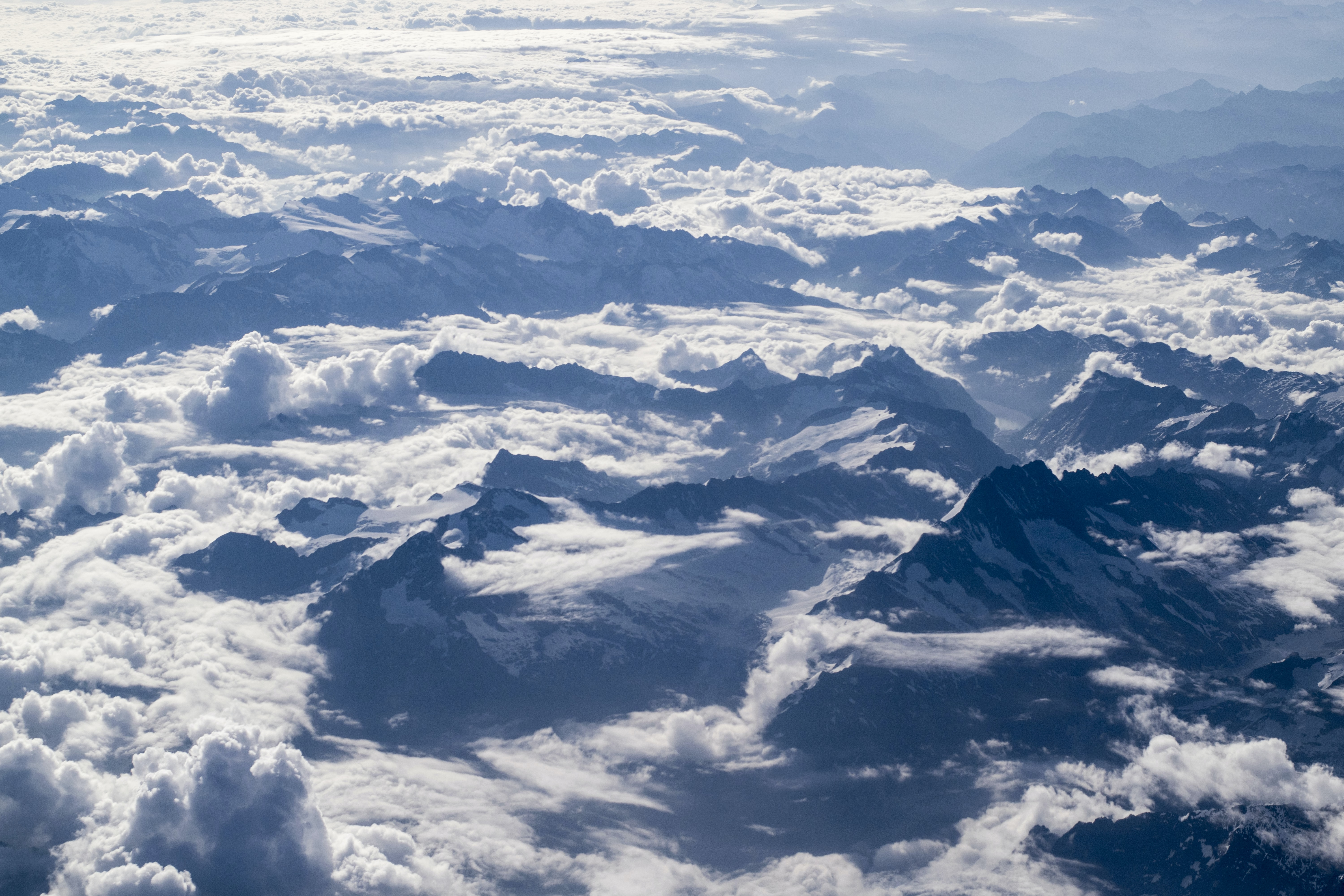 An aerial shot of sharp mountain ridges emerging from a sea of clouds