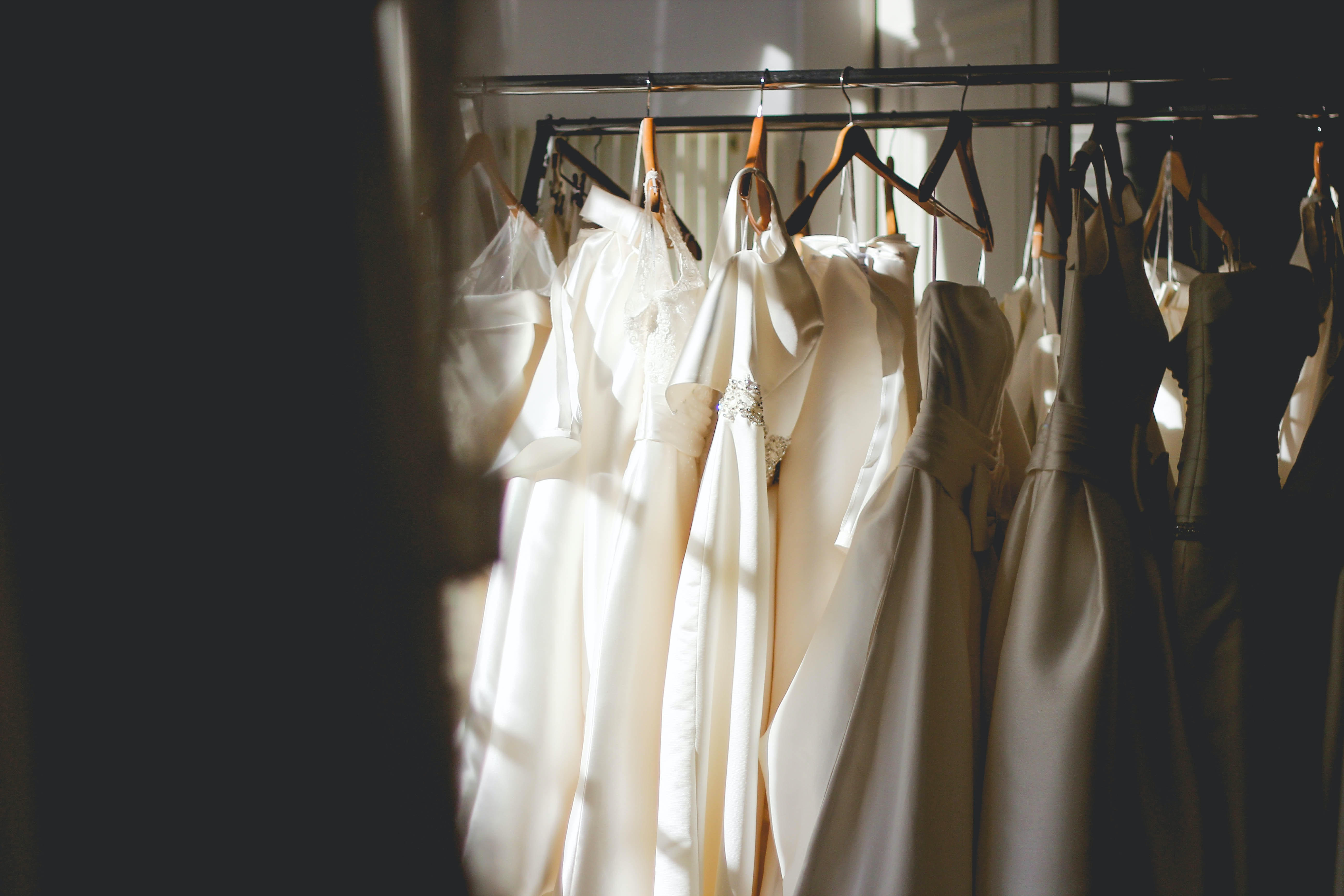 White and beige dresses on hangers in a store