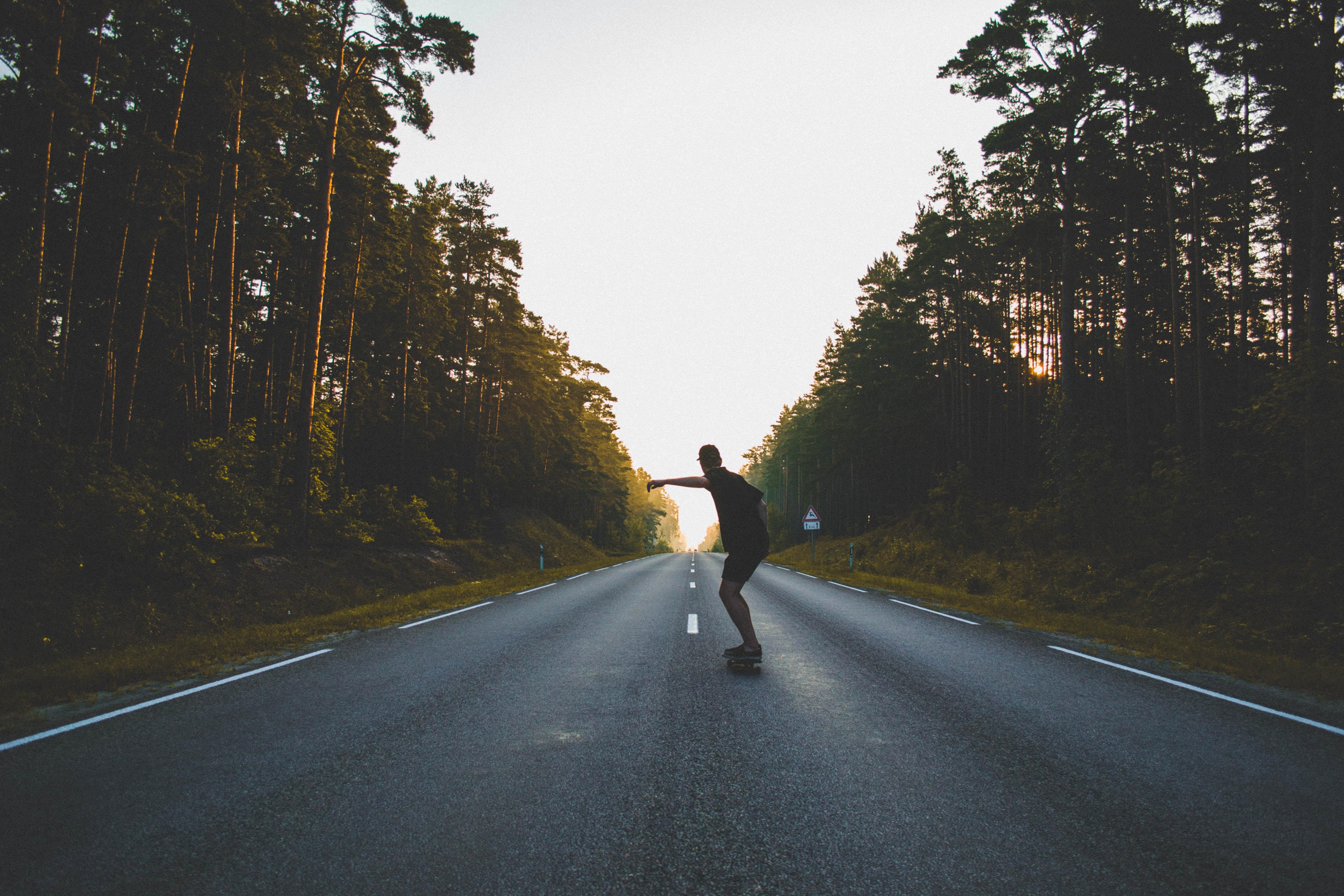 Man skateboarding on asphalt next to forest during sunset