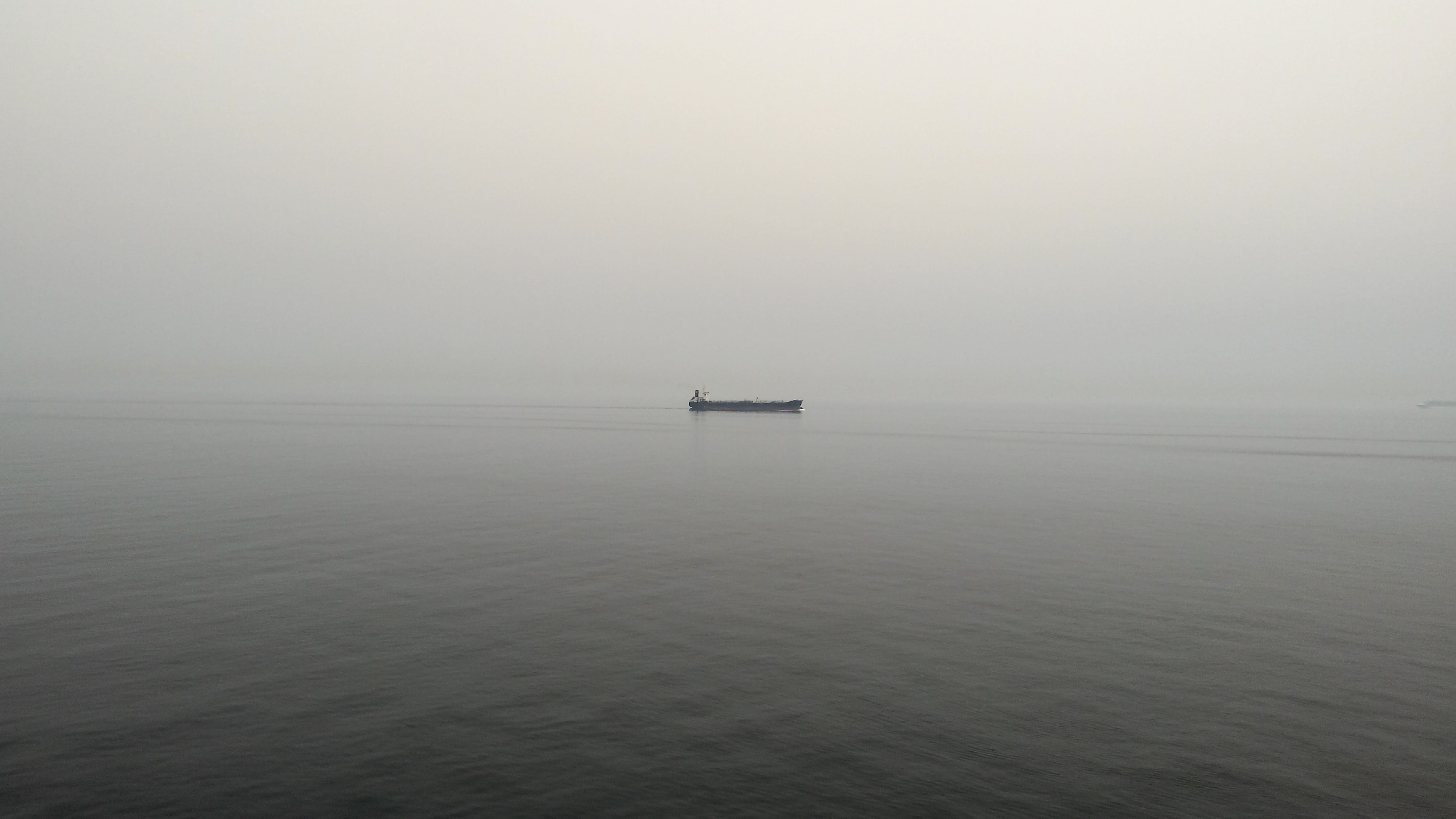 Boat alone on calm gray waters on an overcast foggy morning