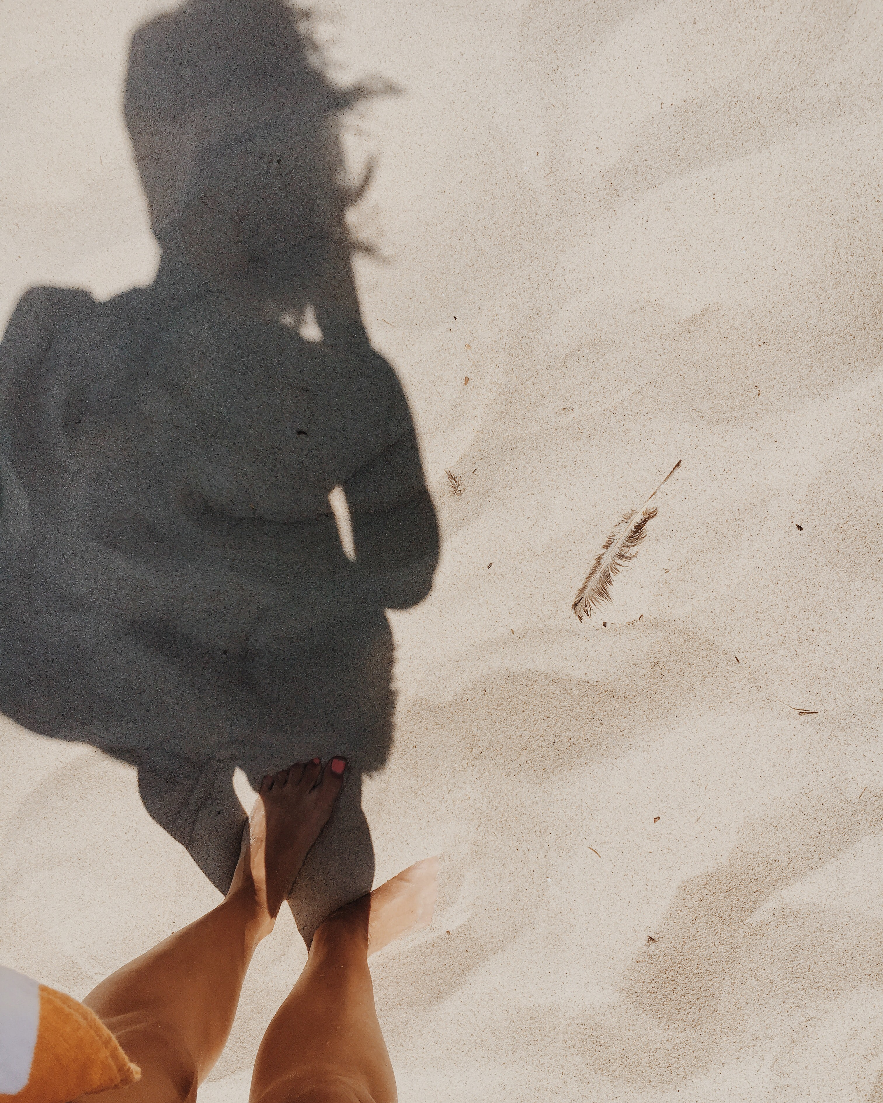 The shadow of a woman standing in the sand on a beach.