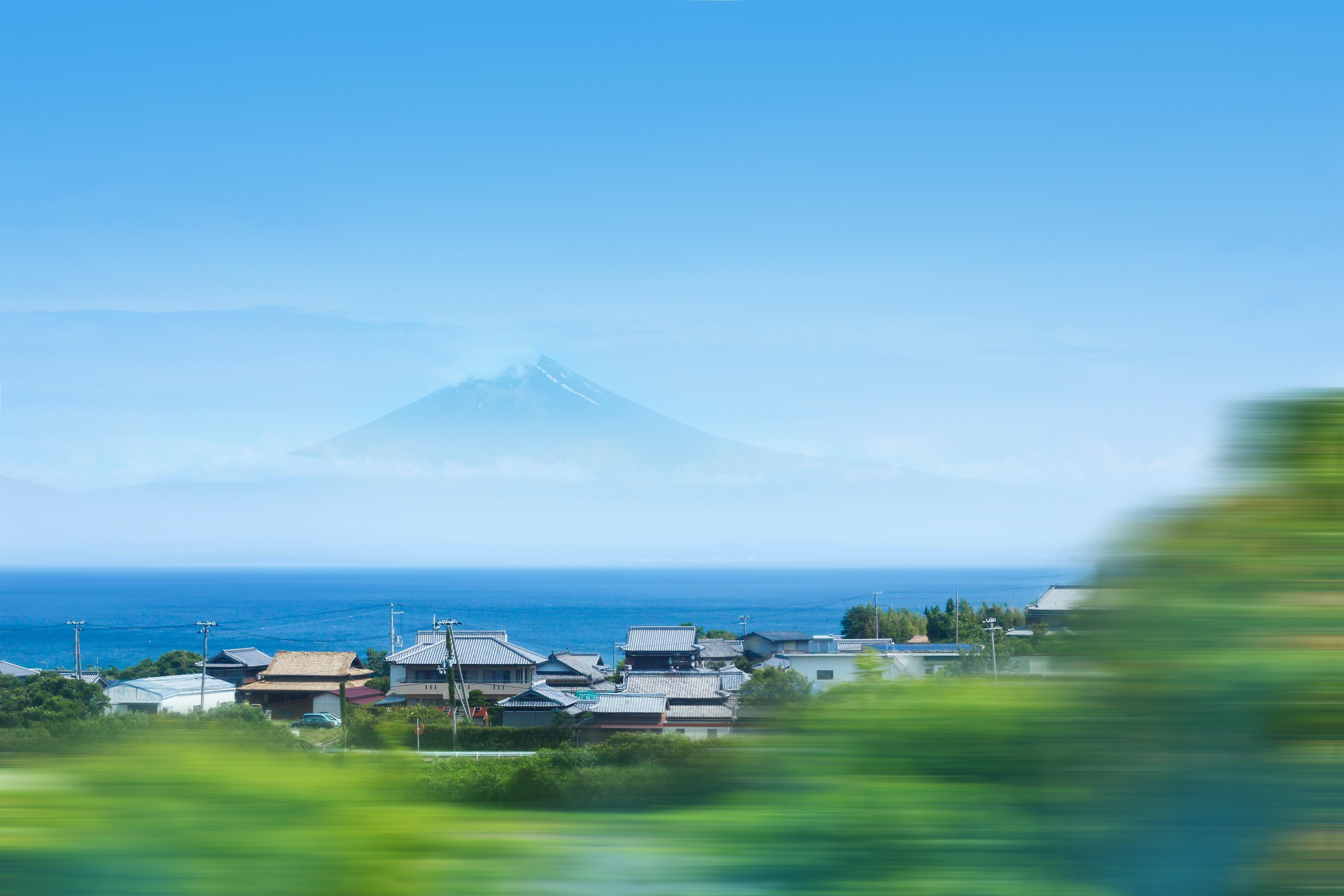 timelapse photo of house near ocean across Mt. Fuji