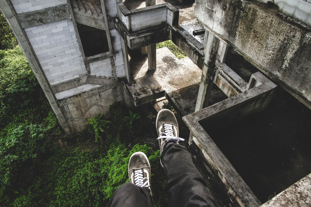 person sitting on gray abandoned building