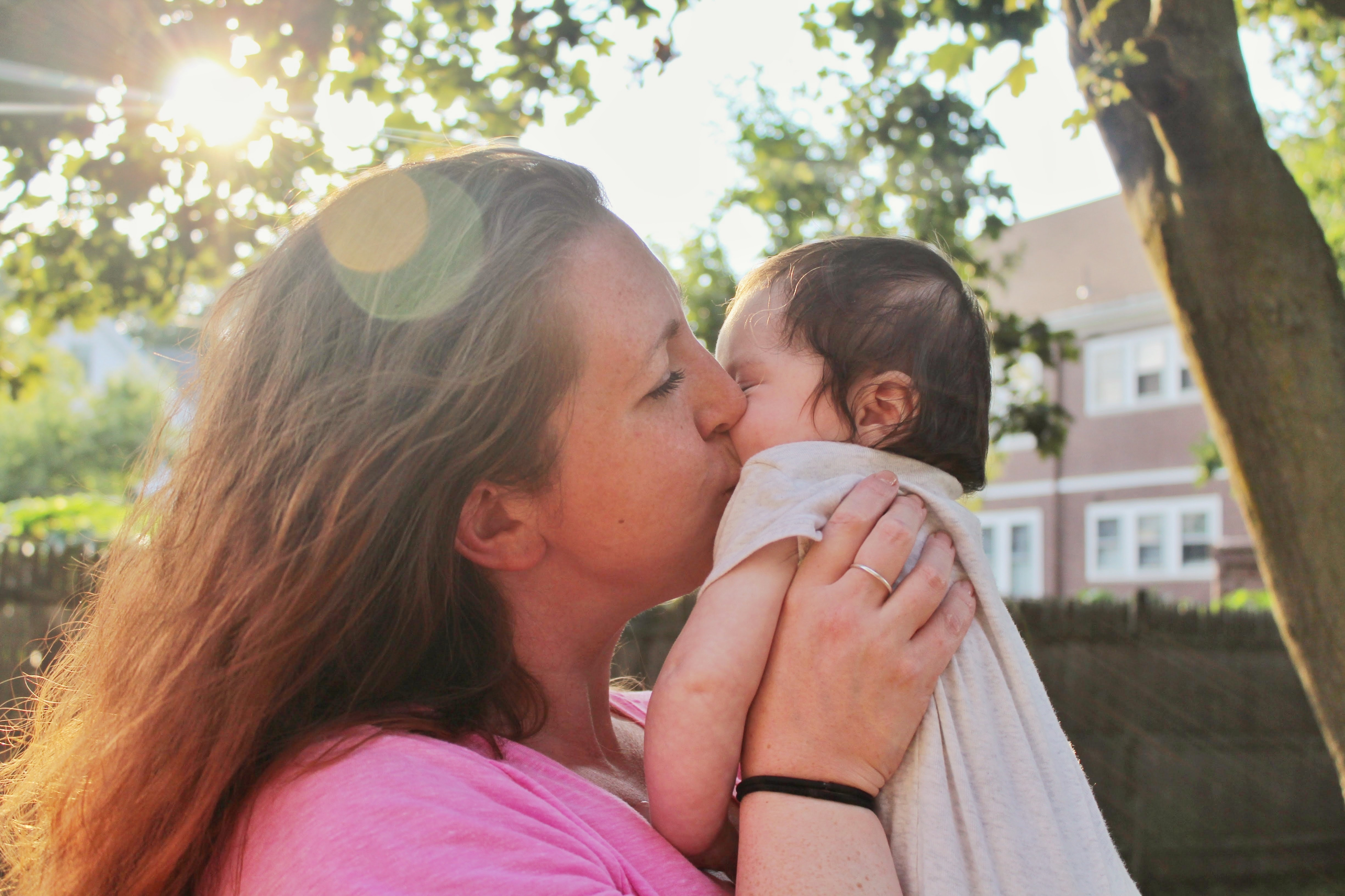 A woman kissing an infant on the cheek.