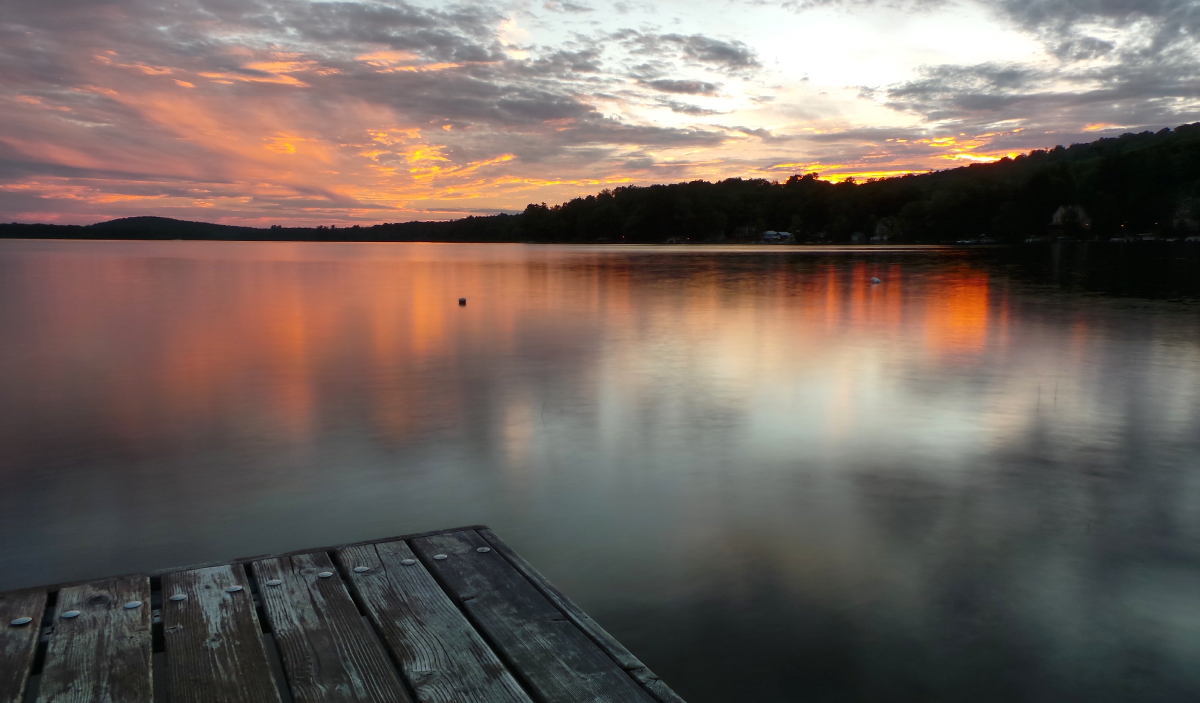 An orange and blue sunset reflecting upon a calm lake, seen from a wooden pier