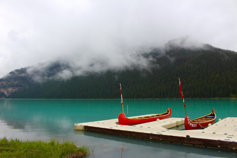 two red boats on body of water