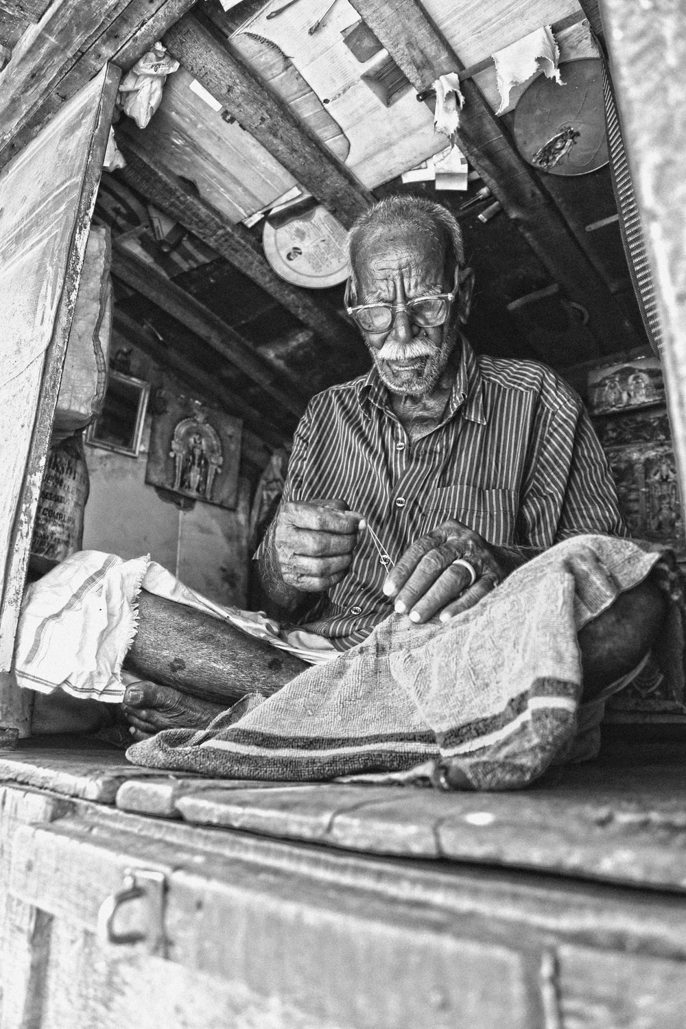 grayscale photo of man sewing textile while sitting on floor