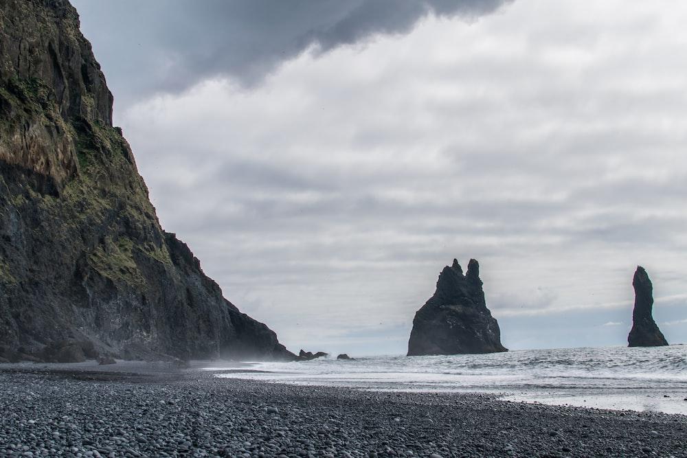 mountain near seashore under gray sky