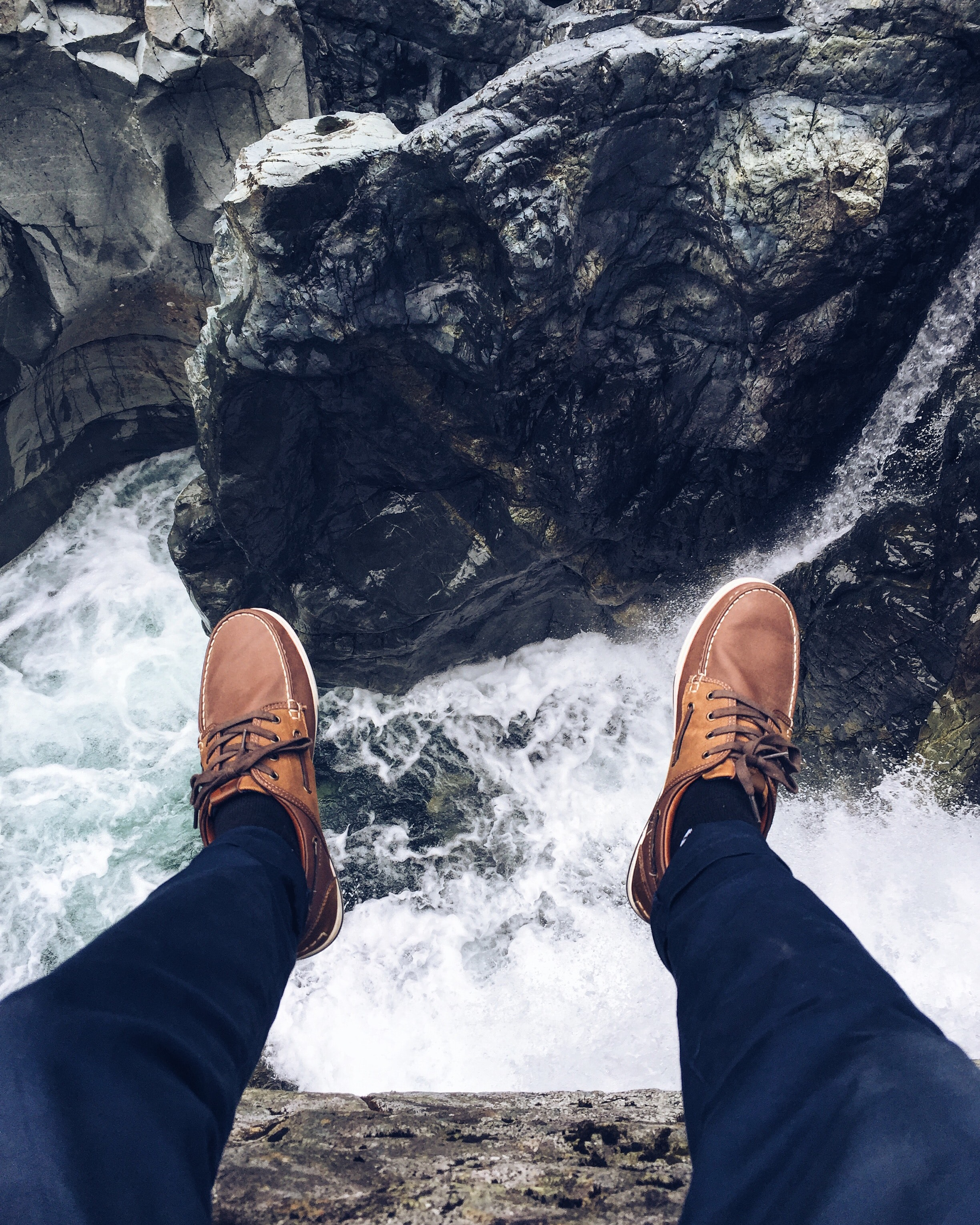 A person's feet in leather shoes dangling off a rock ledge over a fast-flowing creek