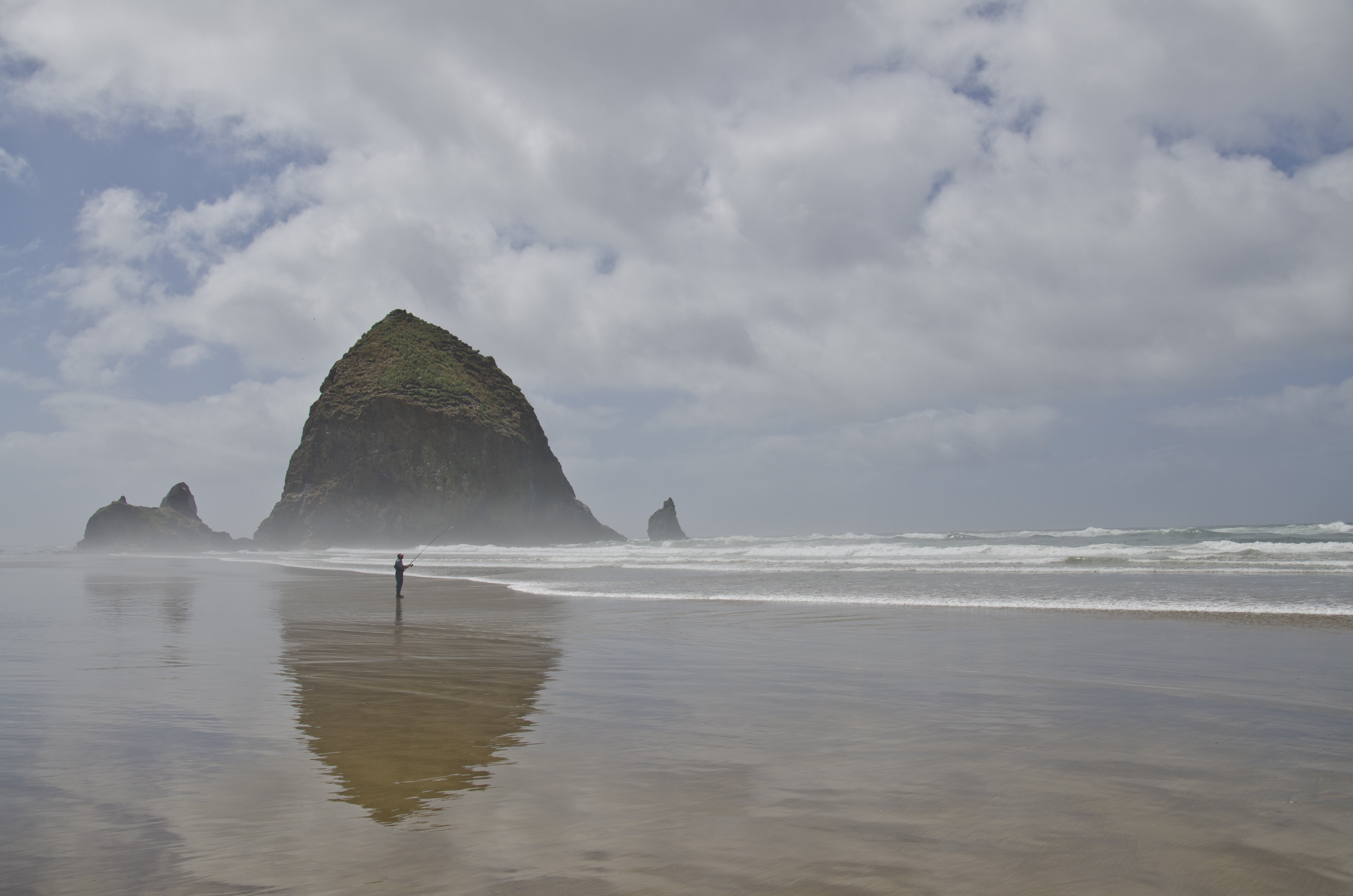Person fishing on the wet sand beach with the big rock formation in background at Cannon Beach
