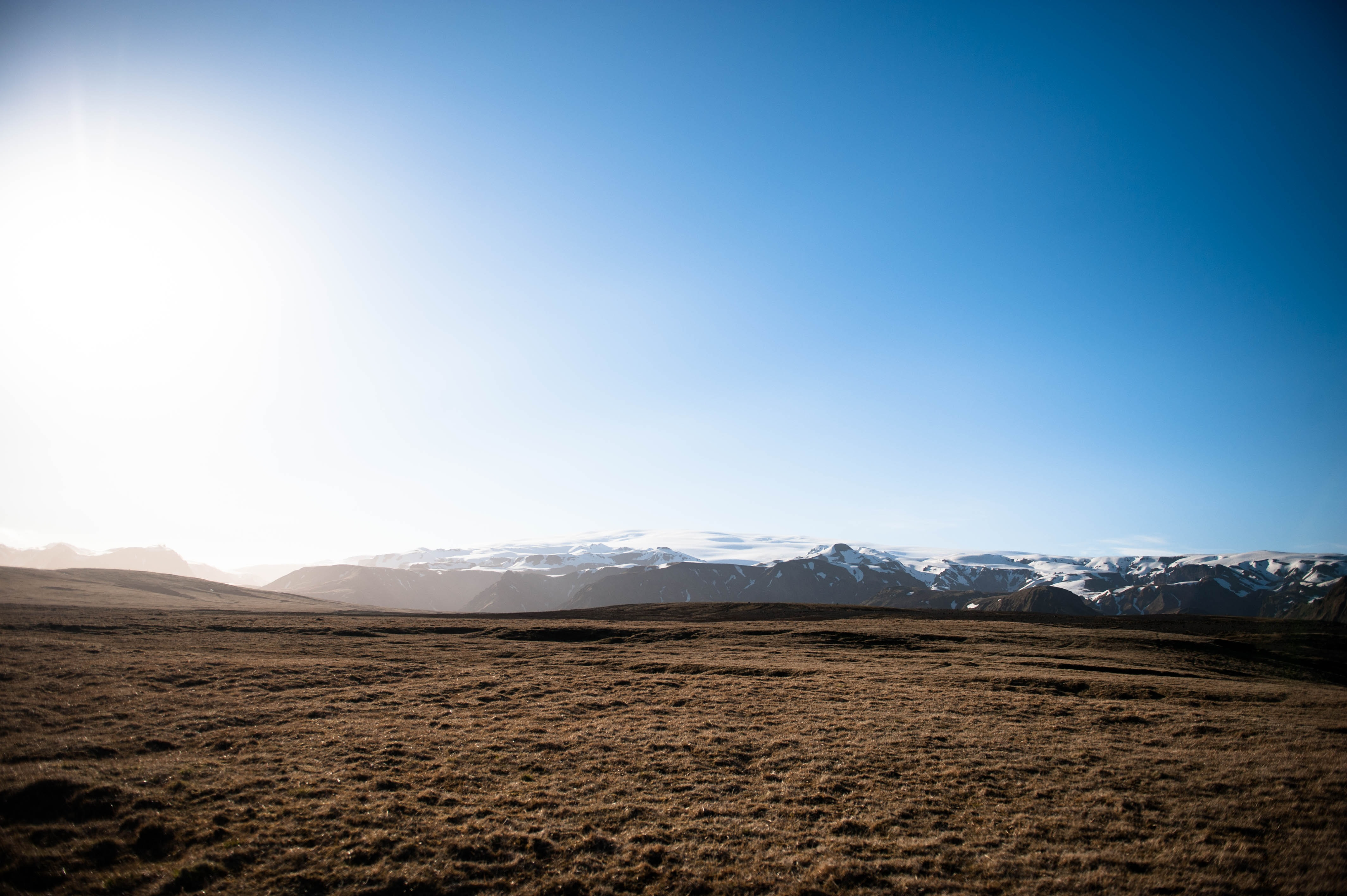 A barren plain with snowy mountains on the horizon