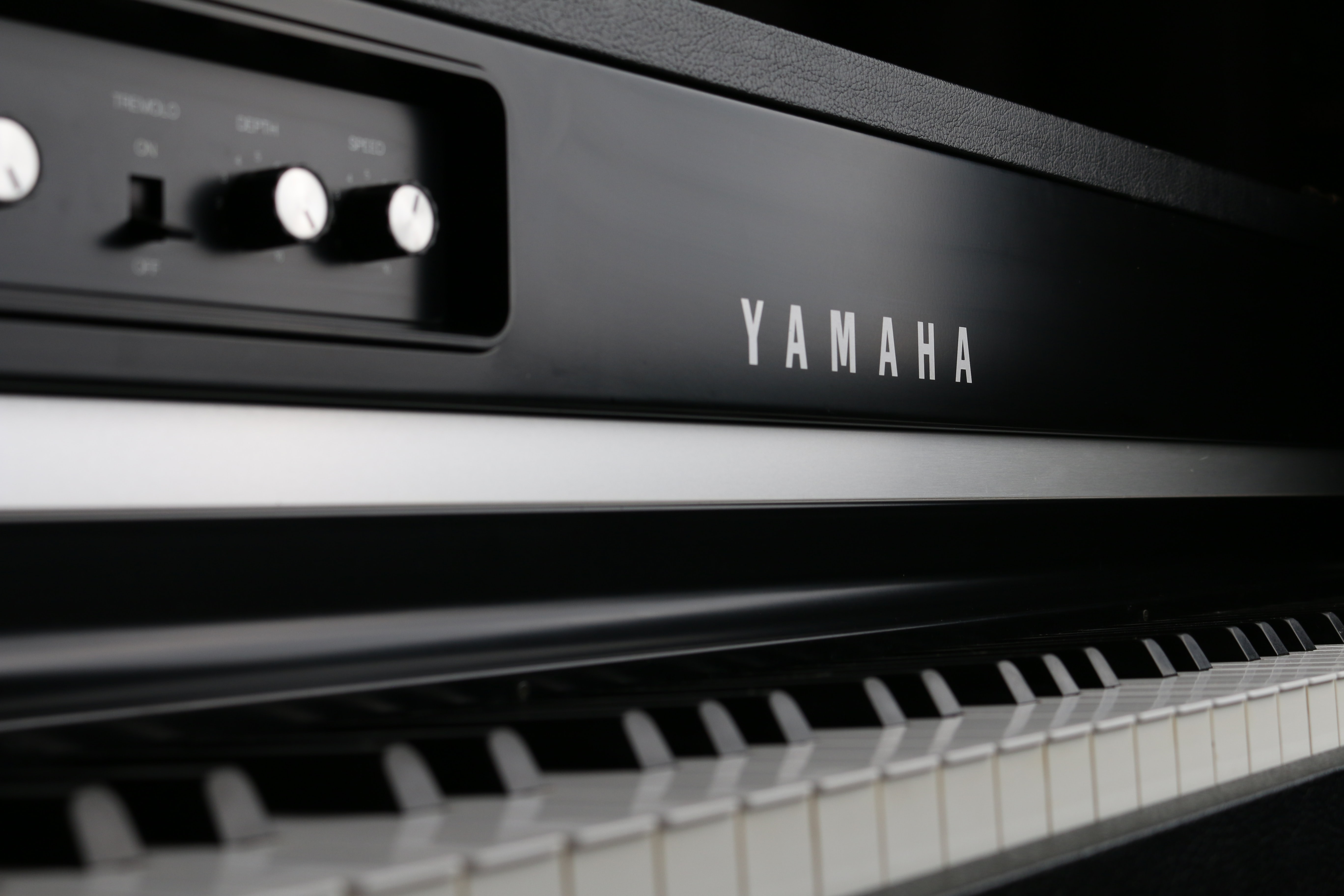A close-up of a black and white Yamaha keyboard