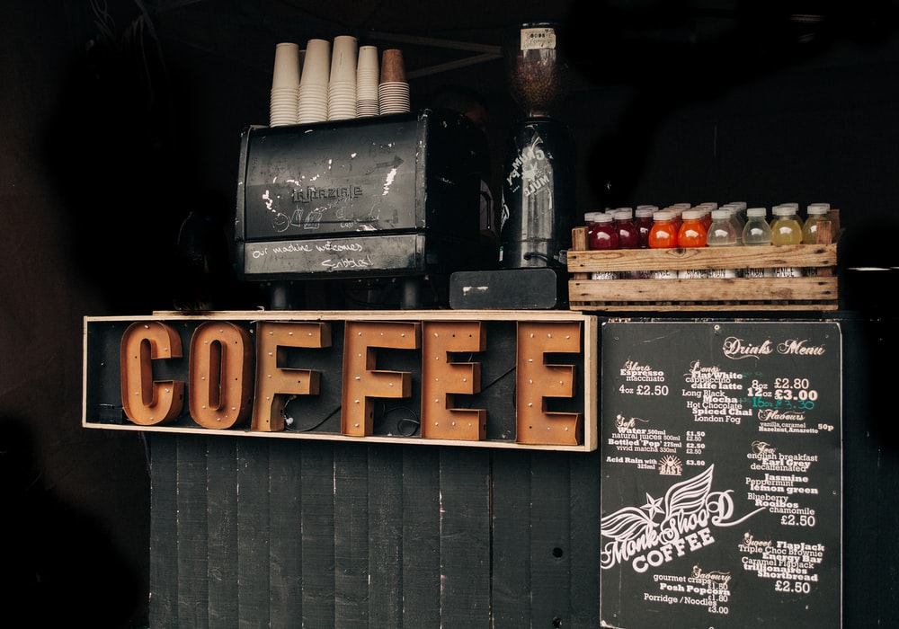 brown coffee signage beside poster