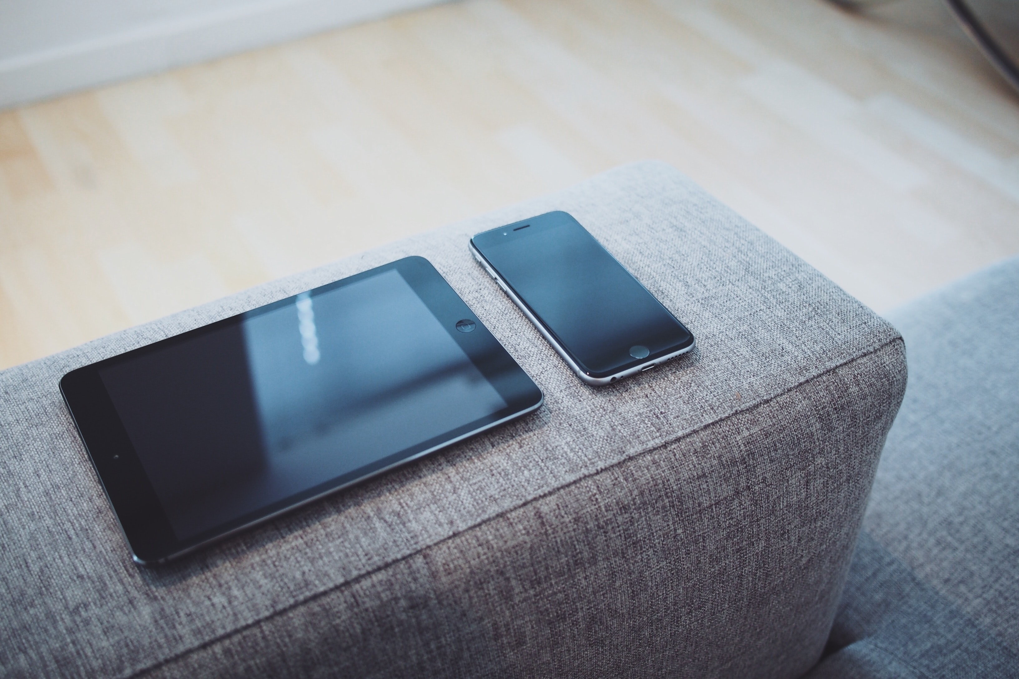 A black iPad mini next to a black iPhone laid out on a on a gray sofa armrest