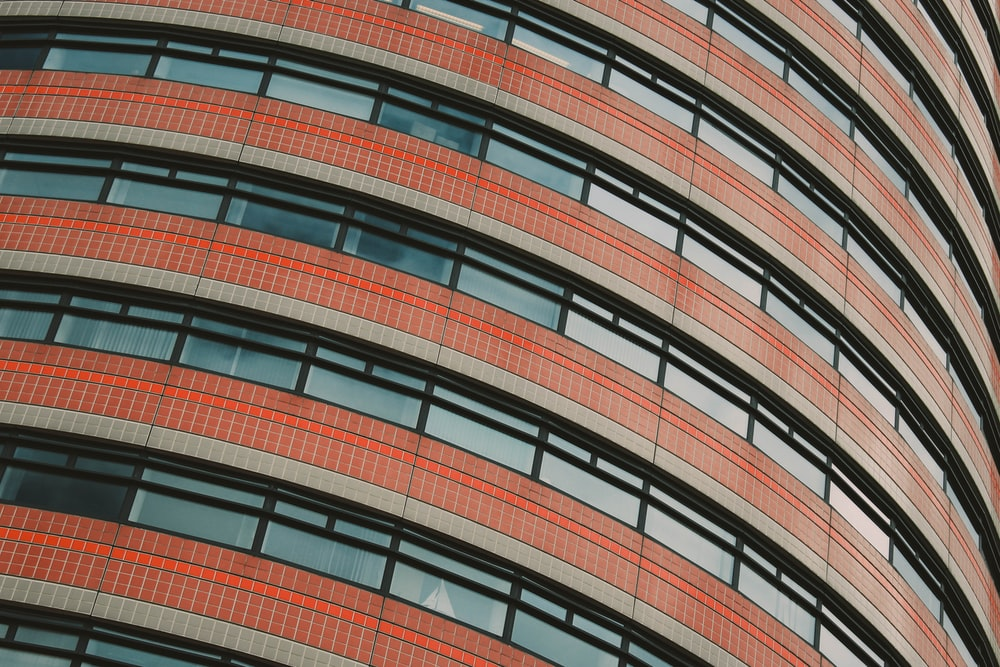 red and clear concrete glass building low angle photography