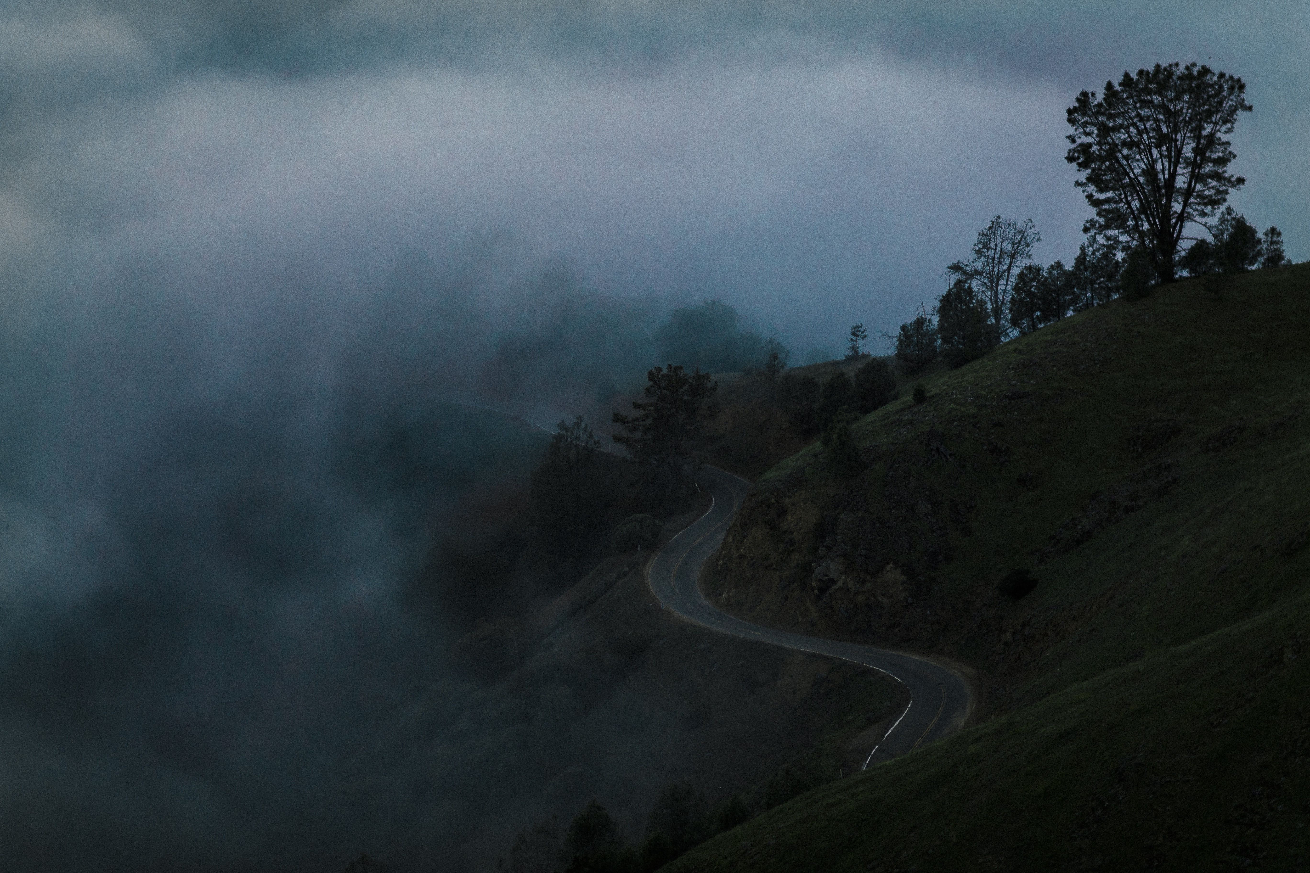 A winding road along a hill under thick mist