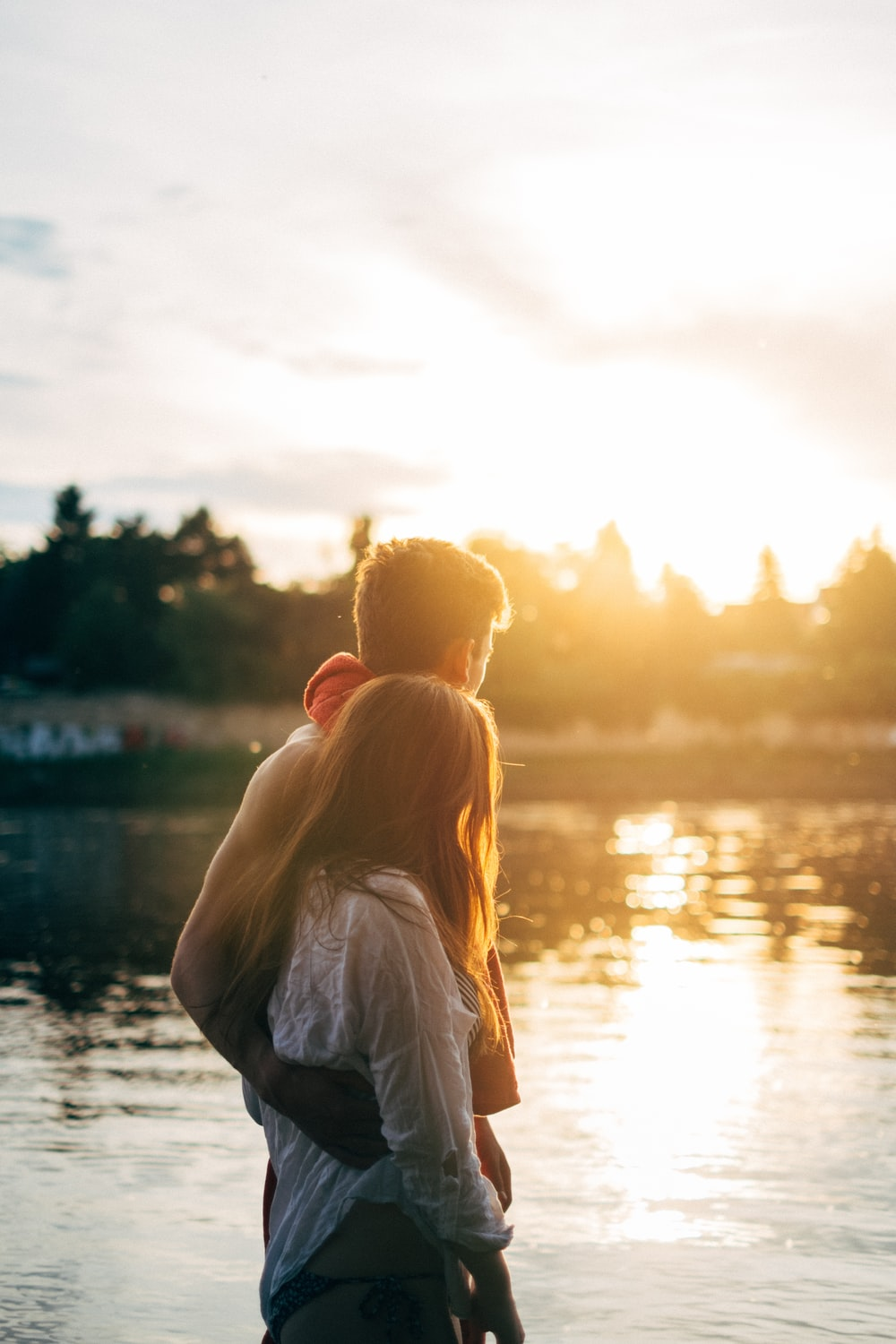 couple walking on lake side watching sunset close-up photo