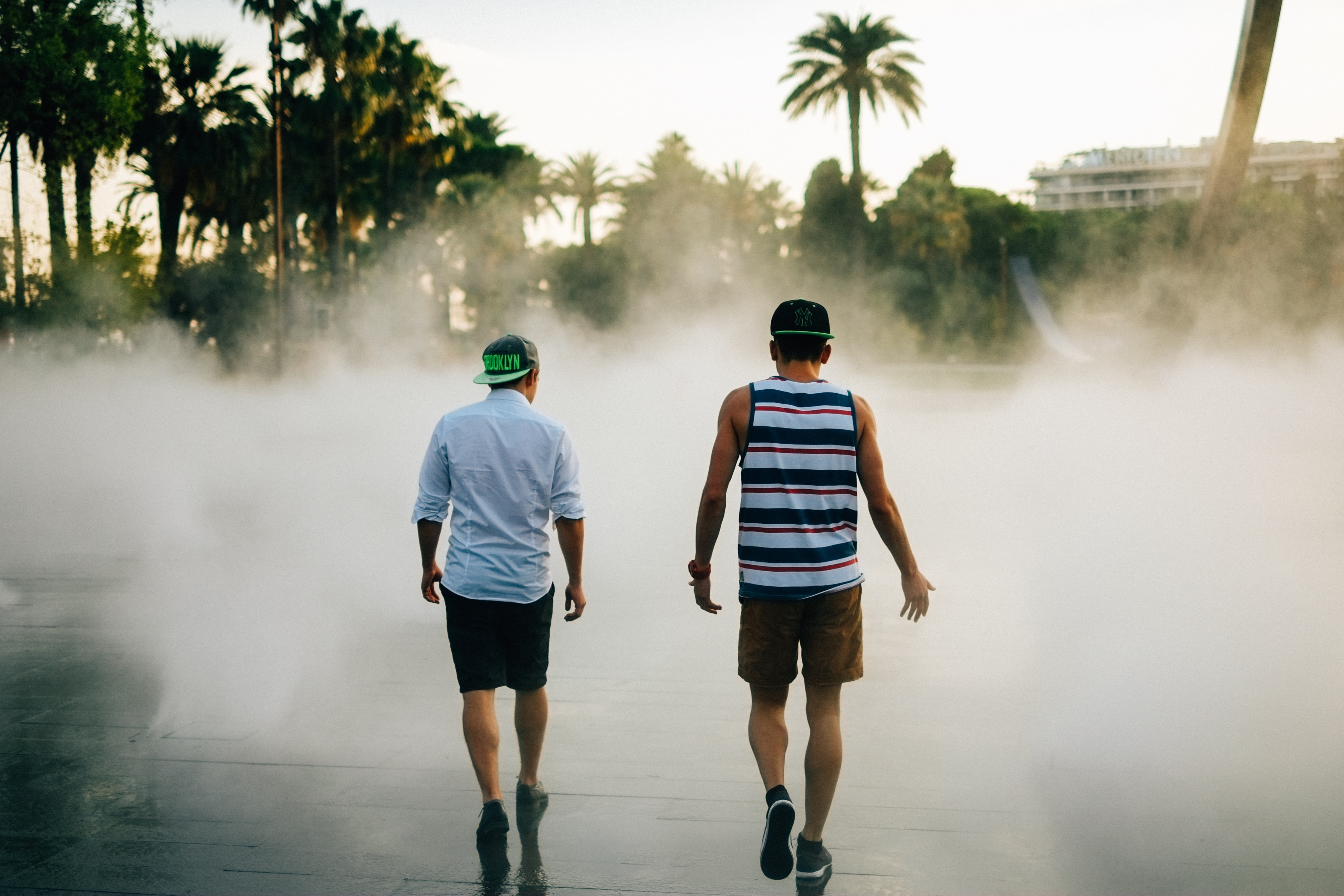 Young men walk through mist towards palm trees in the city