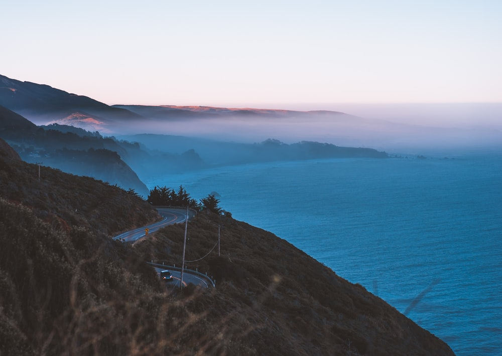 body of water and road hills surrounded by fogs