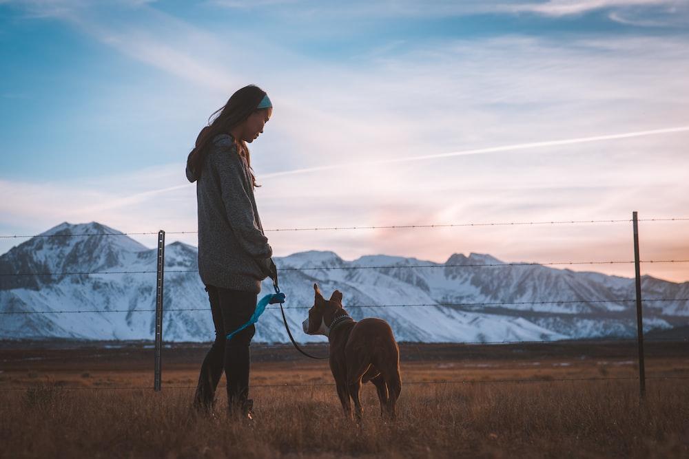 man holding dog leash on brown grass