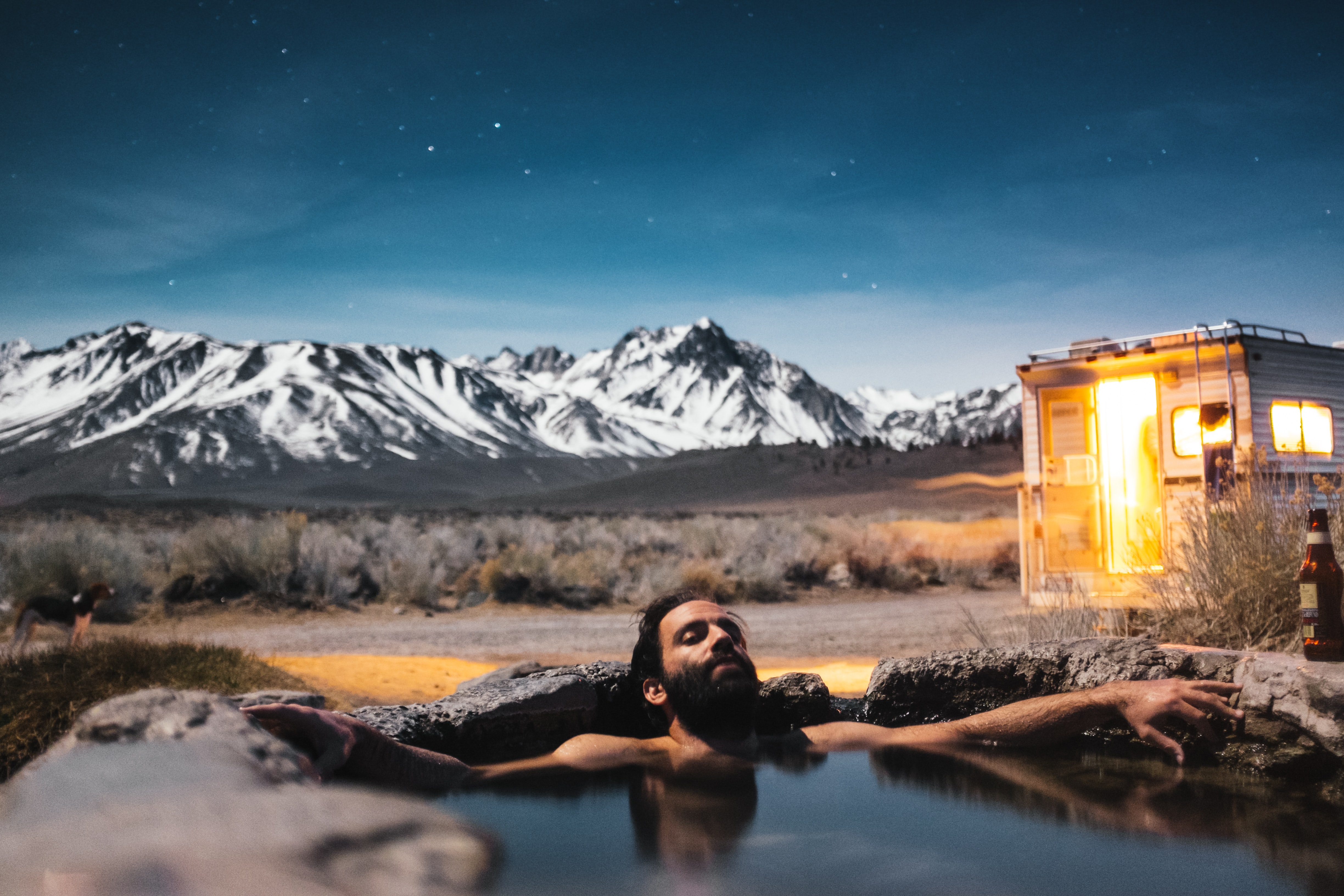 A bearded man relaxing in hot water near an RV with a snow-capped mountain range on the horizon