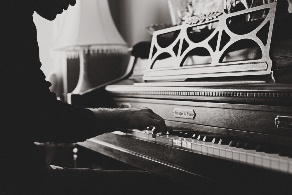 greyscale photo of man playing spinet piano close-up photo
