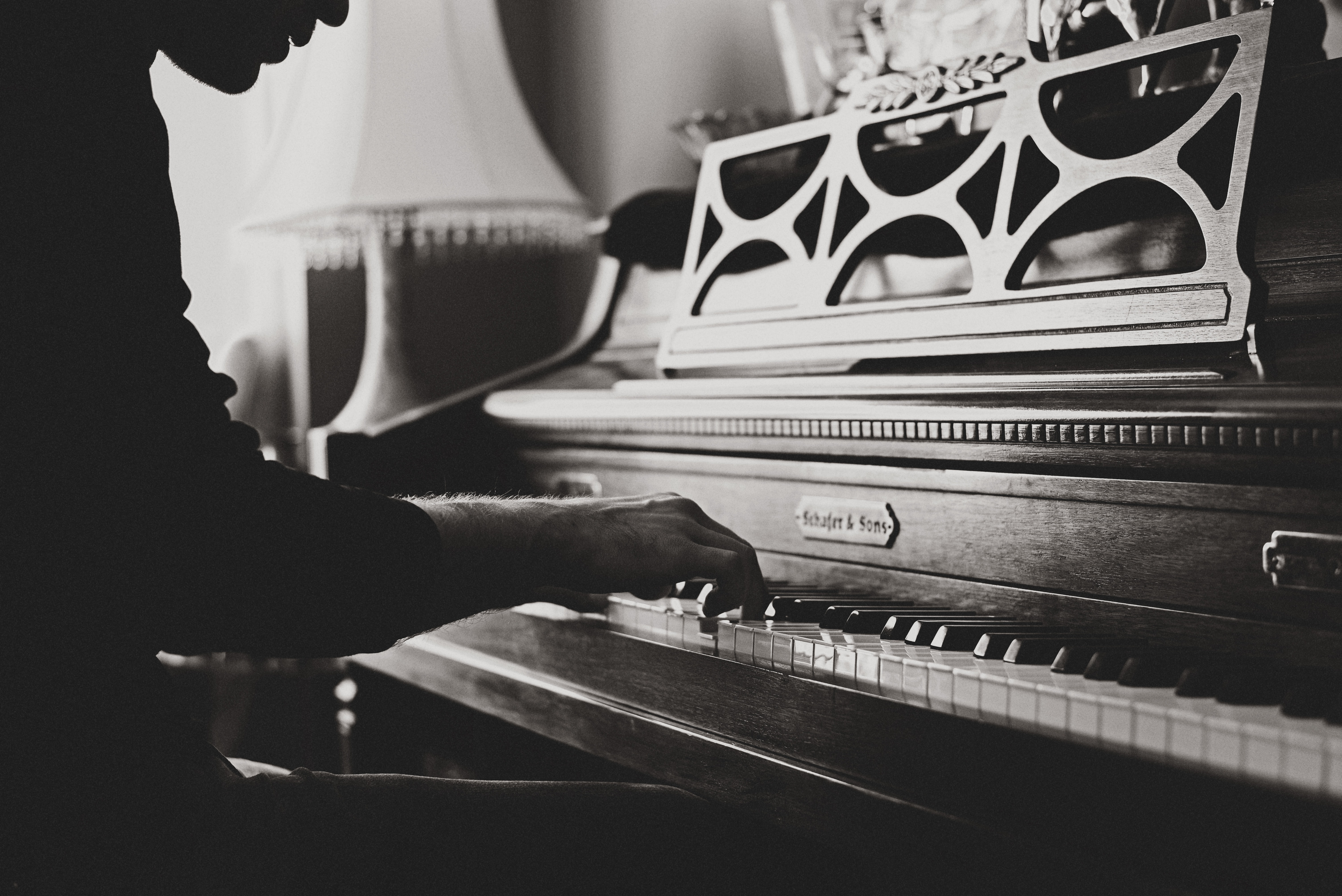 A black-and-white shot of a man playing a vintage piano