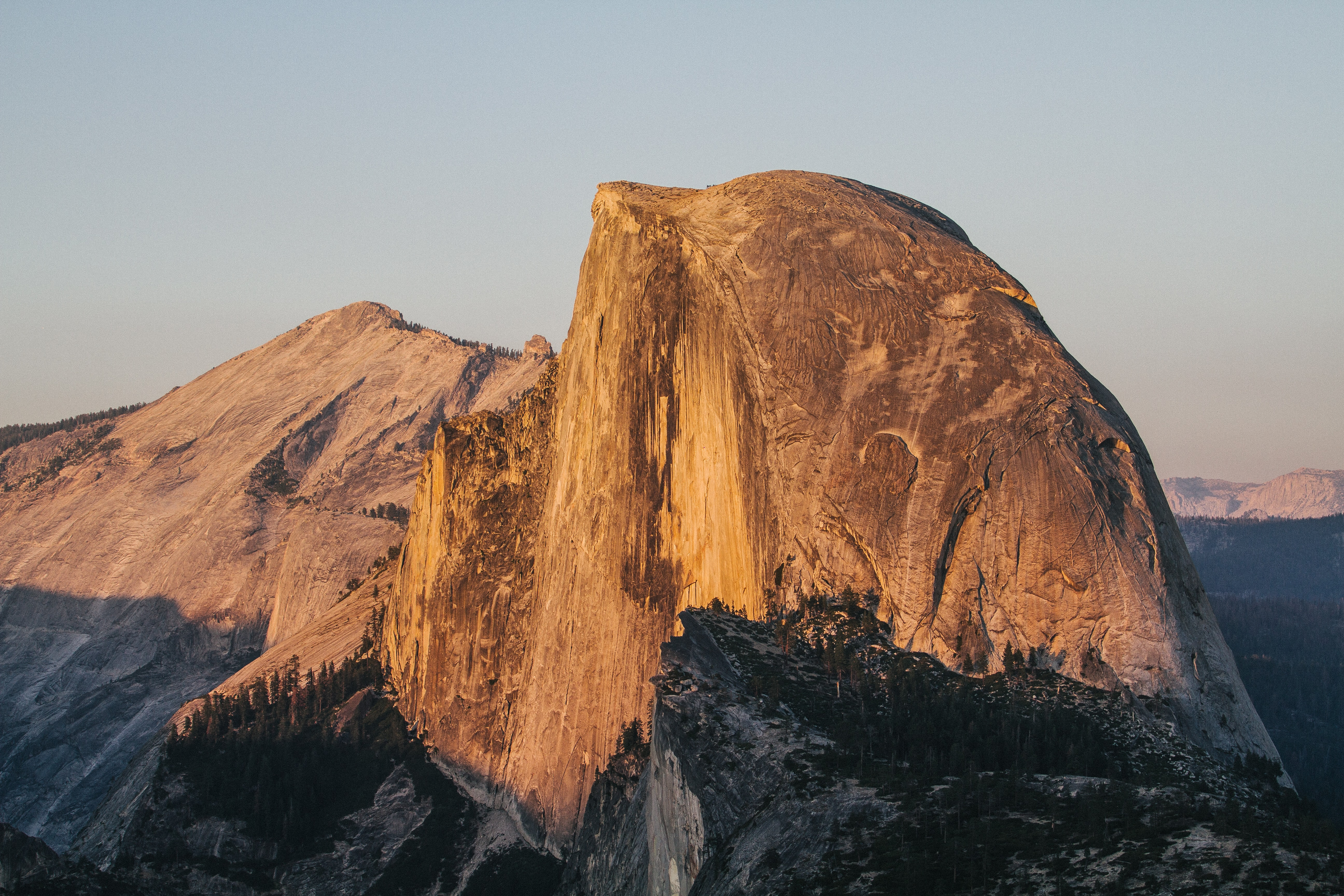 Rocky mountain cliffs of Half Dome at Yosemite National Park illuminated by sunset
