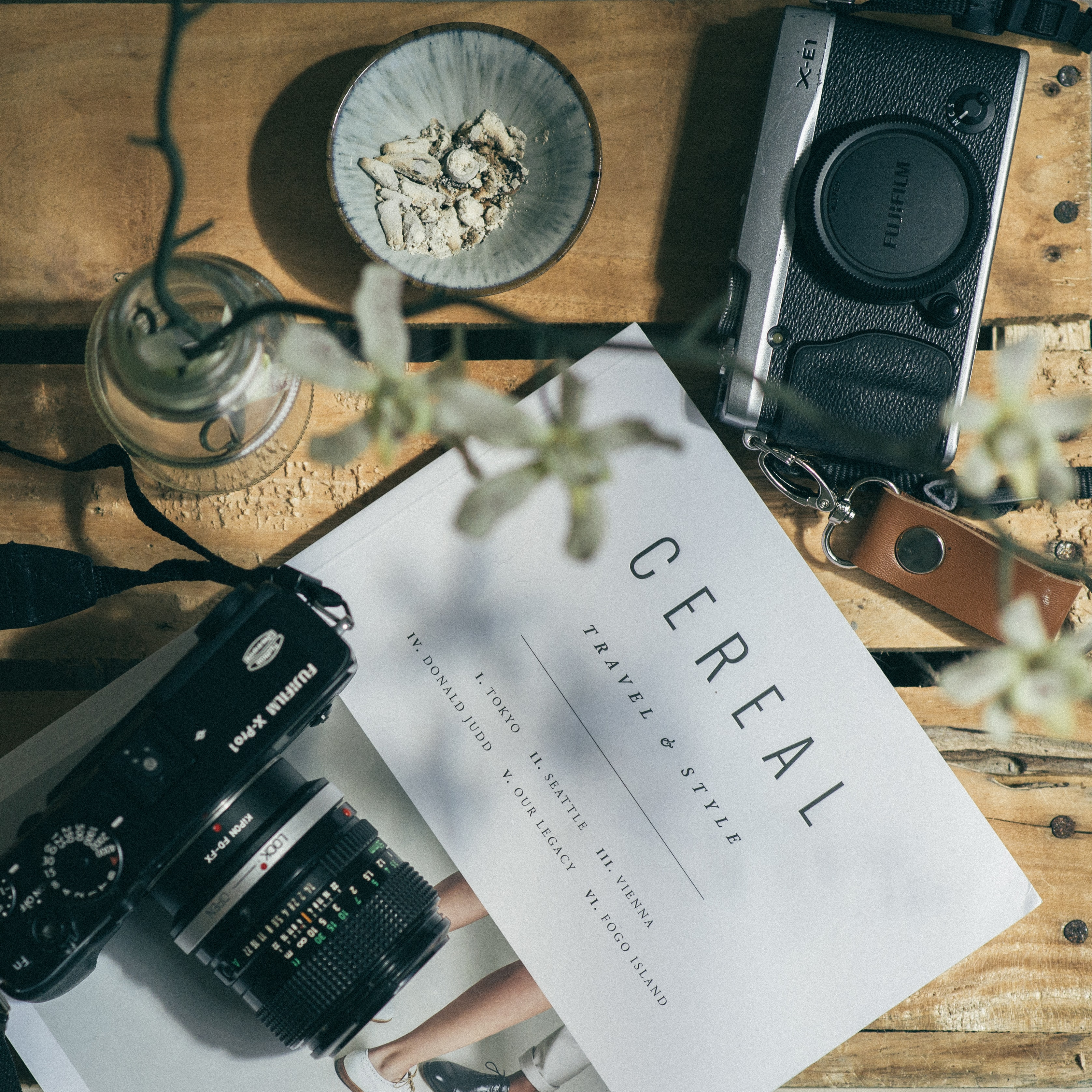 Two Fujifilm cameras, a blue bowl, a flower in a glass vase, and a magazine on a table