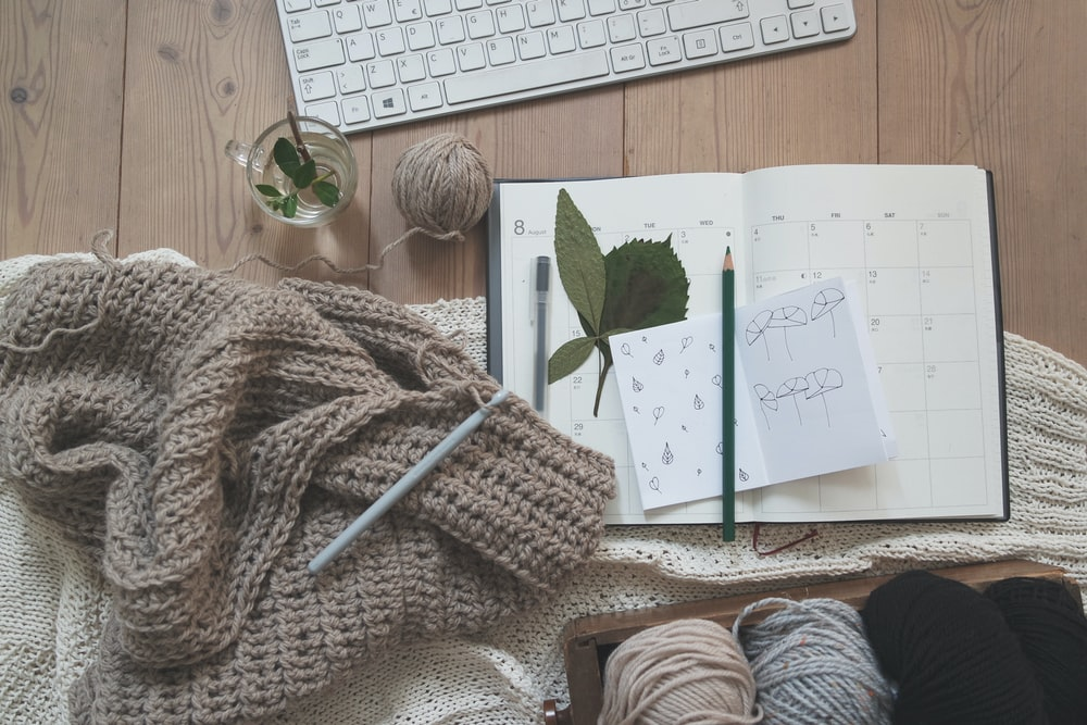 black pencil on white card beside brown knit textile