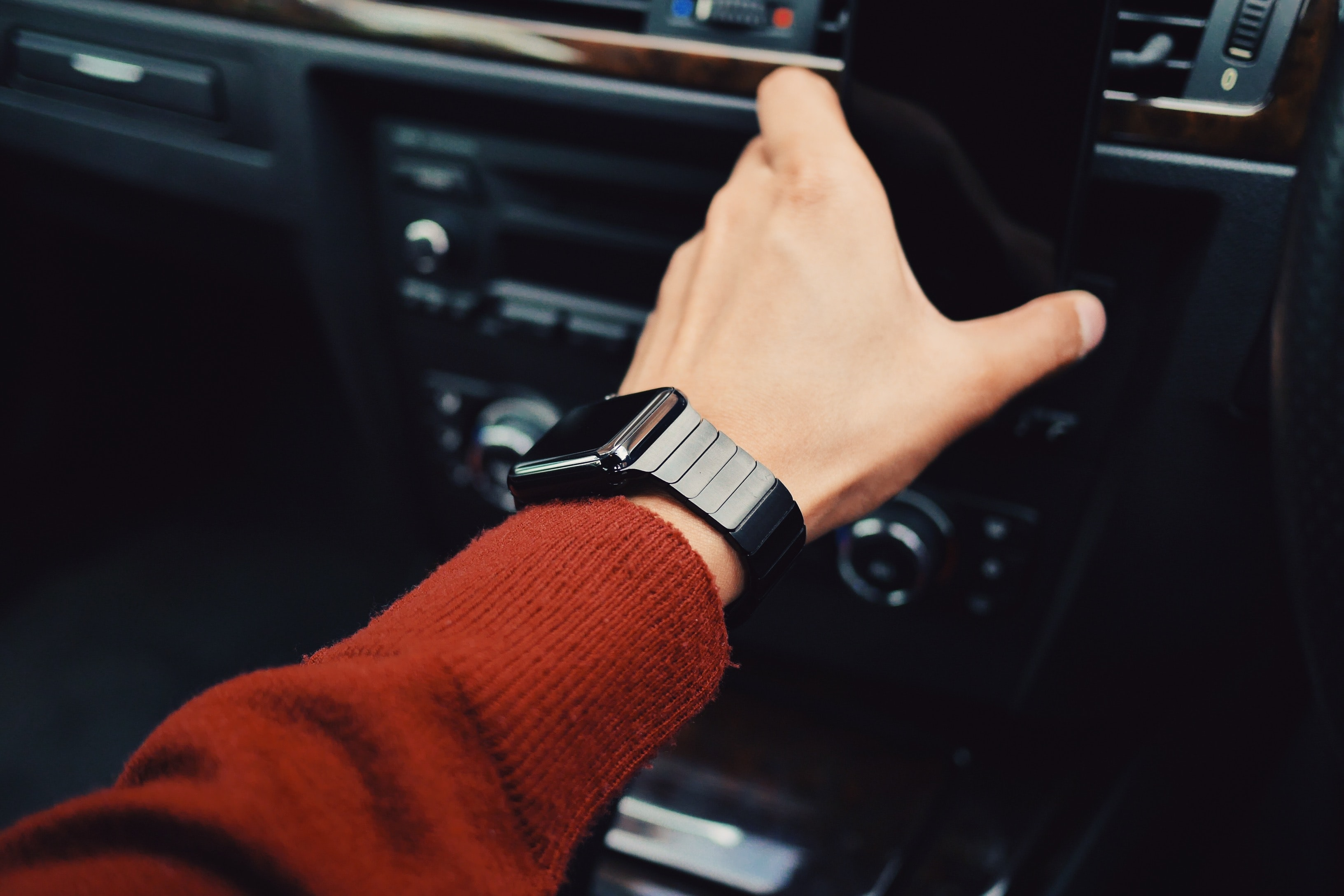 An outstretched hand of a person wearing a red sweater and an Apple Watch inside a car