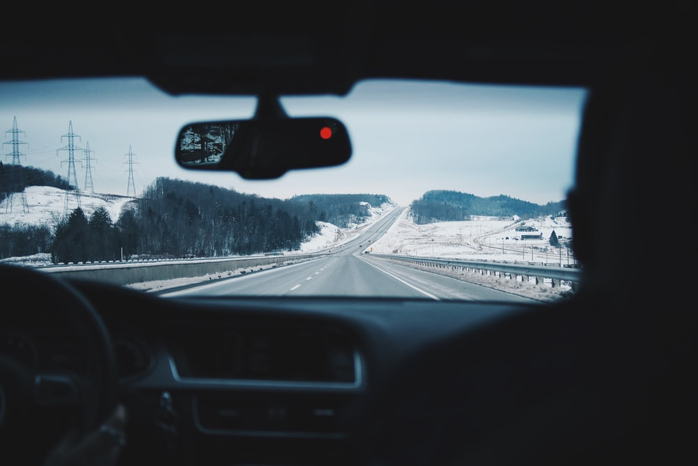 two people inside of car while driving on asphalt road between of land with covered of snow