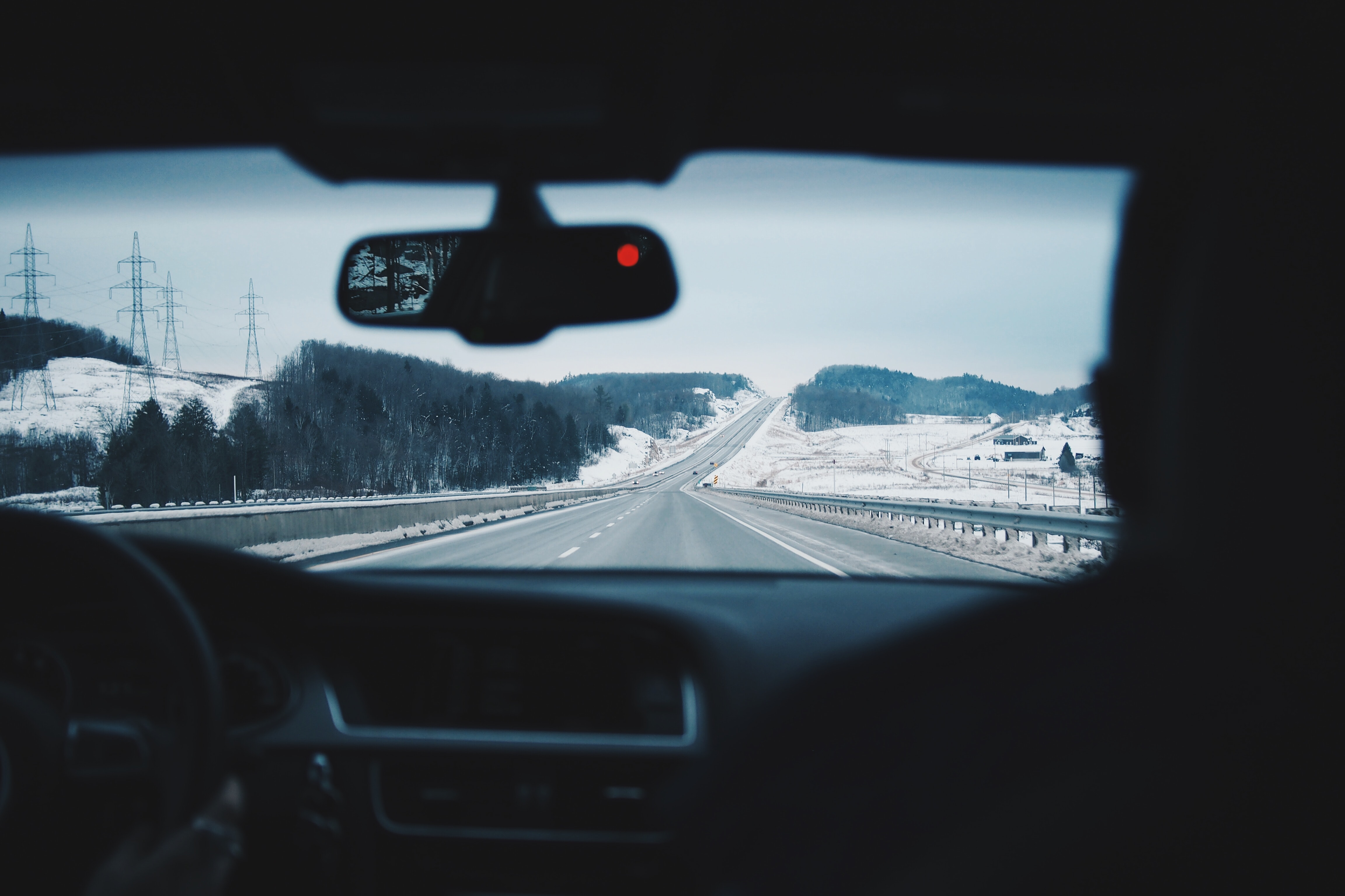 View through the windscreen from the Audi interior on the two-lane highway during Winter.