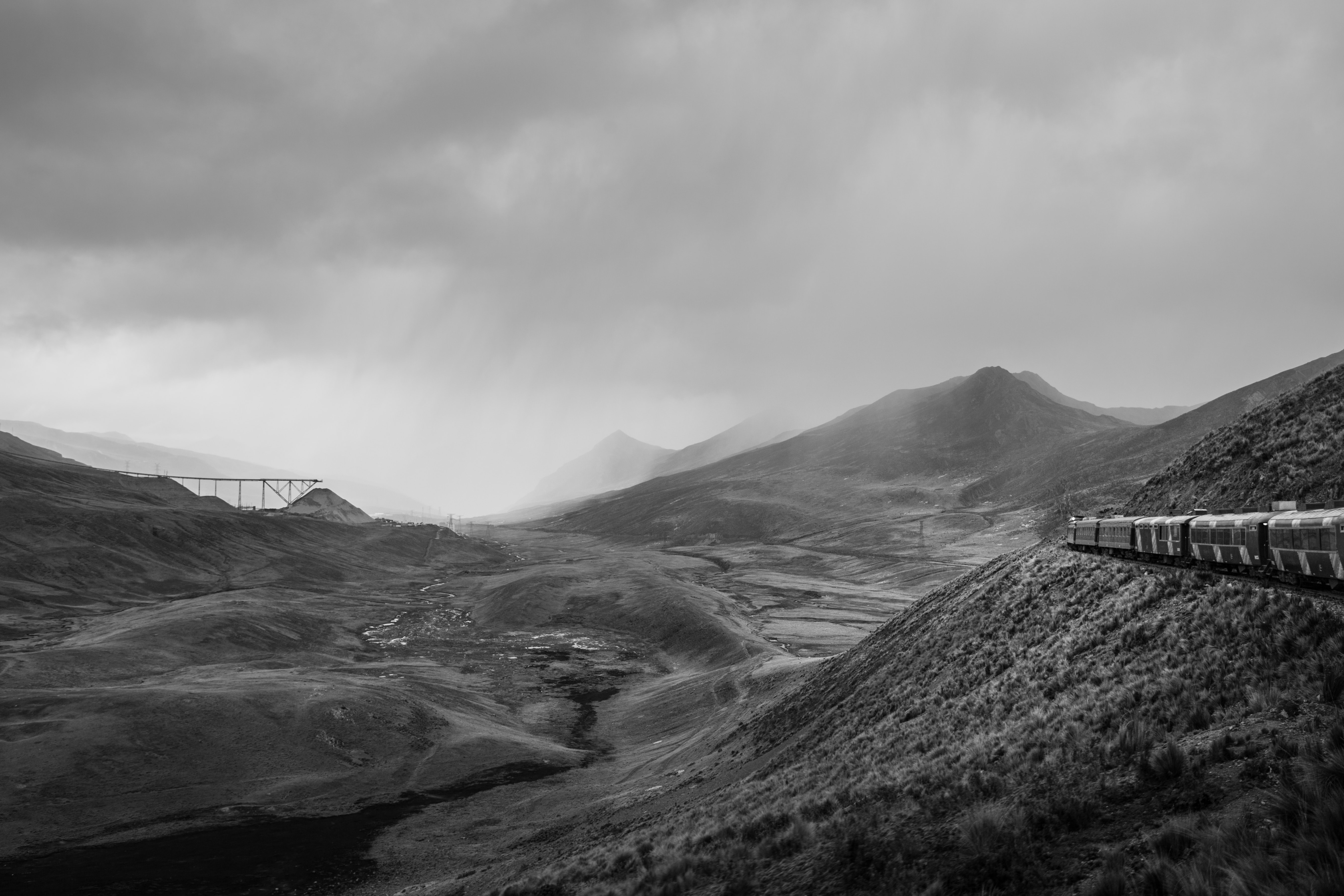 Black and white panoramic shot of train travelling through mountains and rocks with cloudy sky