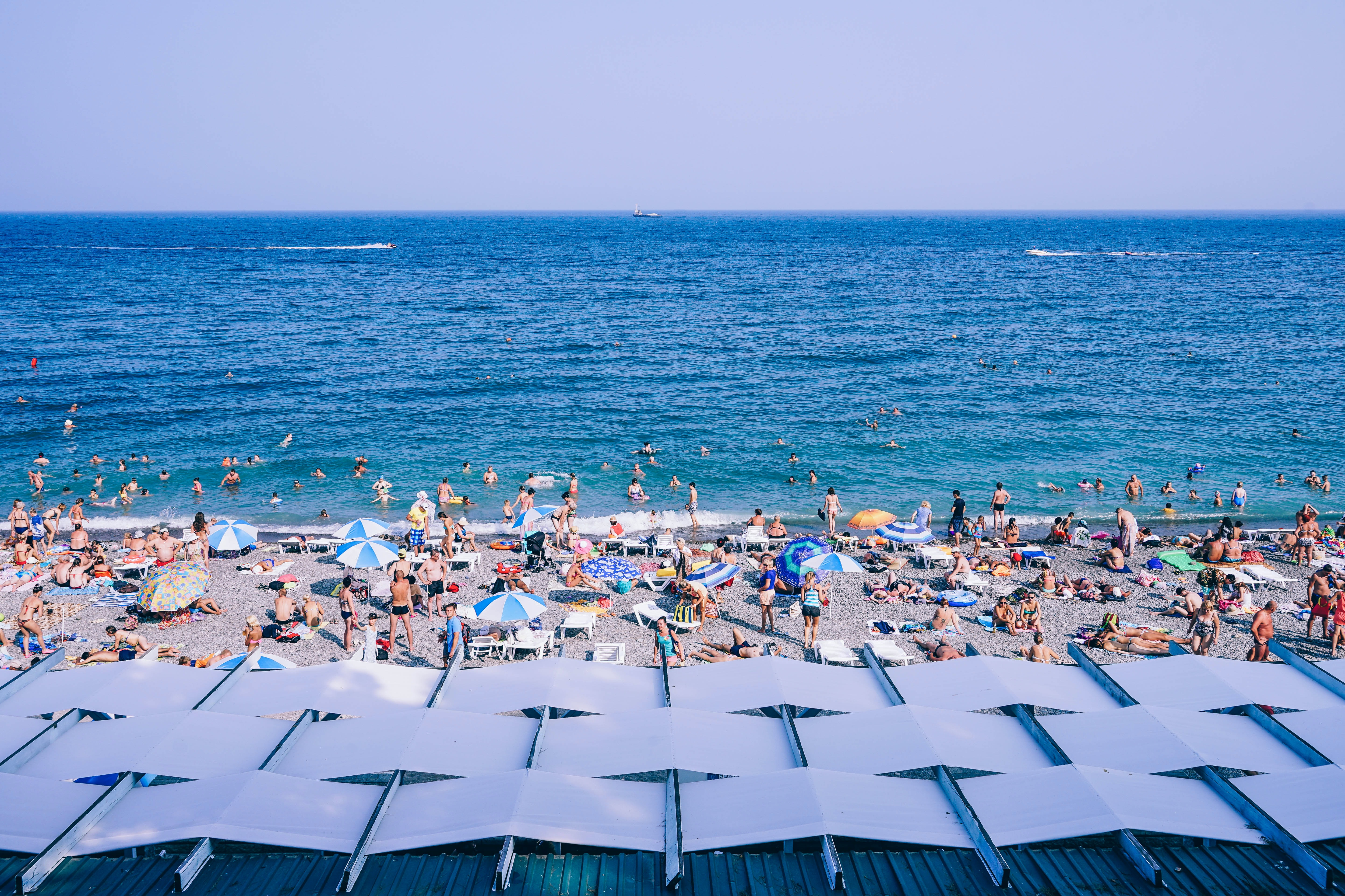View from the back of a sandy beach on the crowd of tourists sunbathing and swimming in the sea