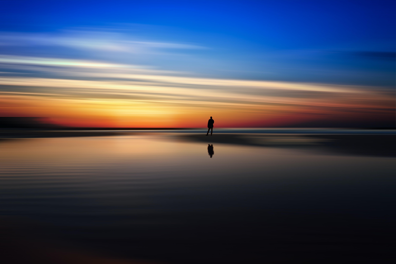 person standing in seashore under horizon