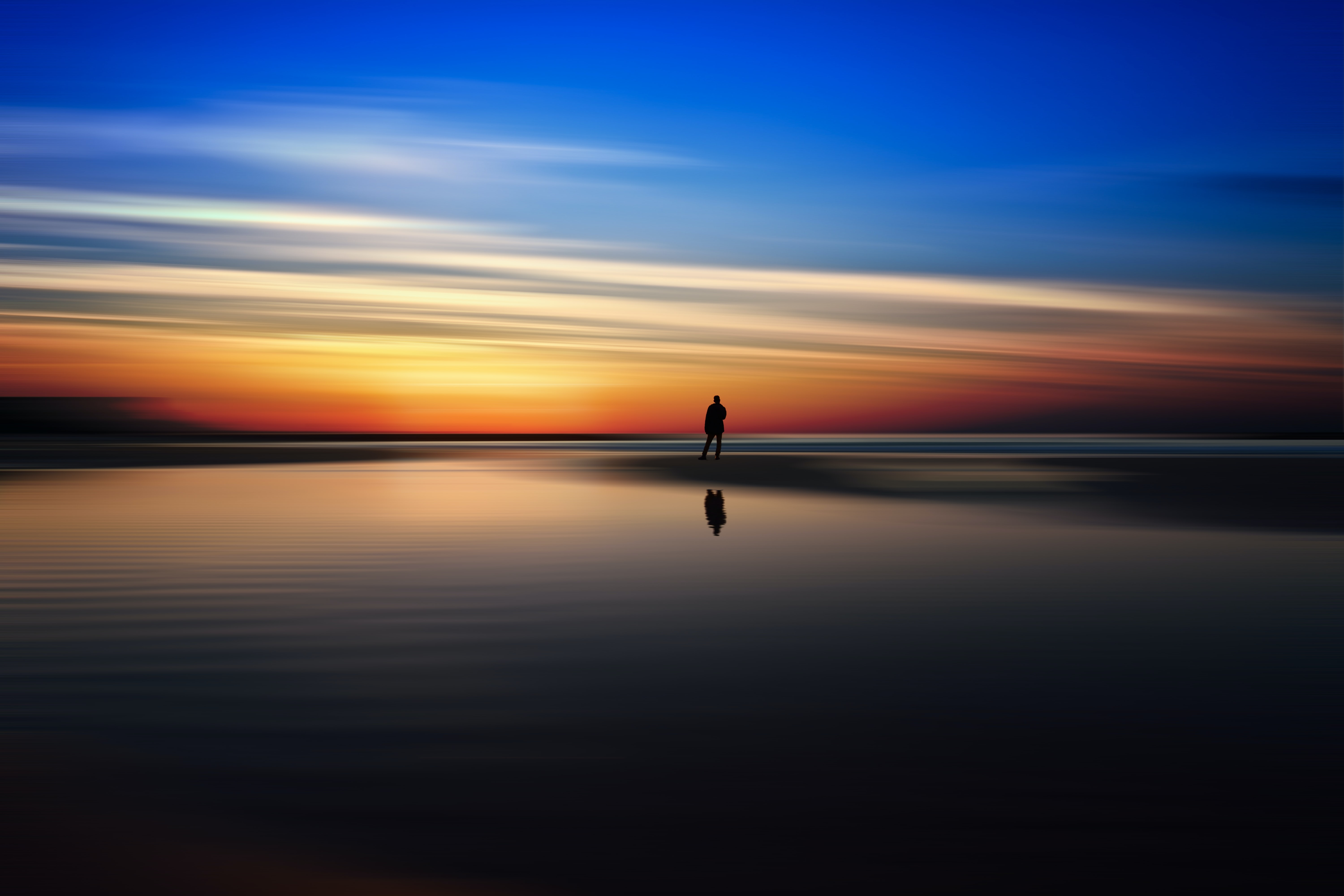 Colorful sunset reflecting off the beach in Tel Aviv-Yafo with person standing in horizon