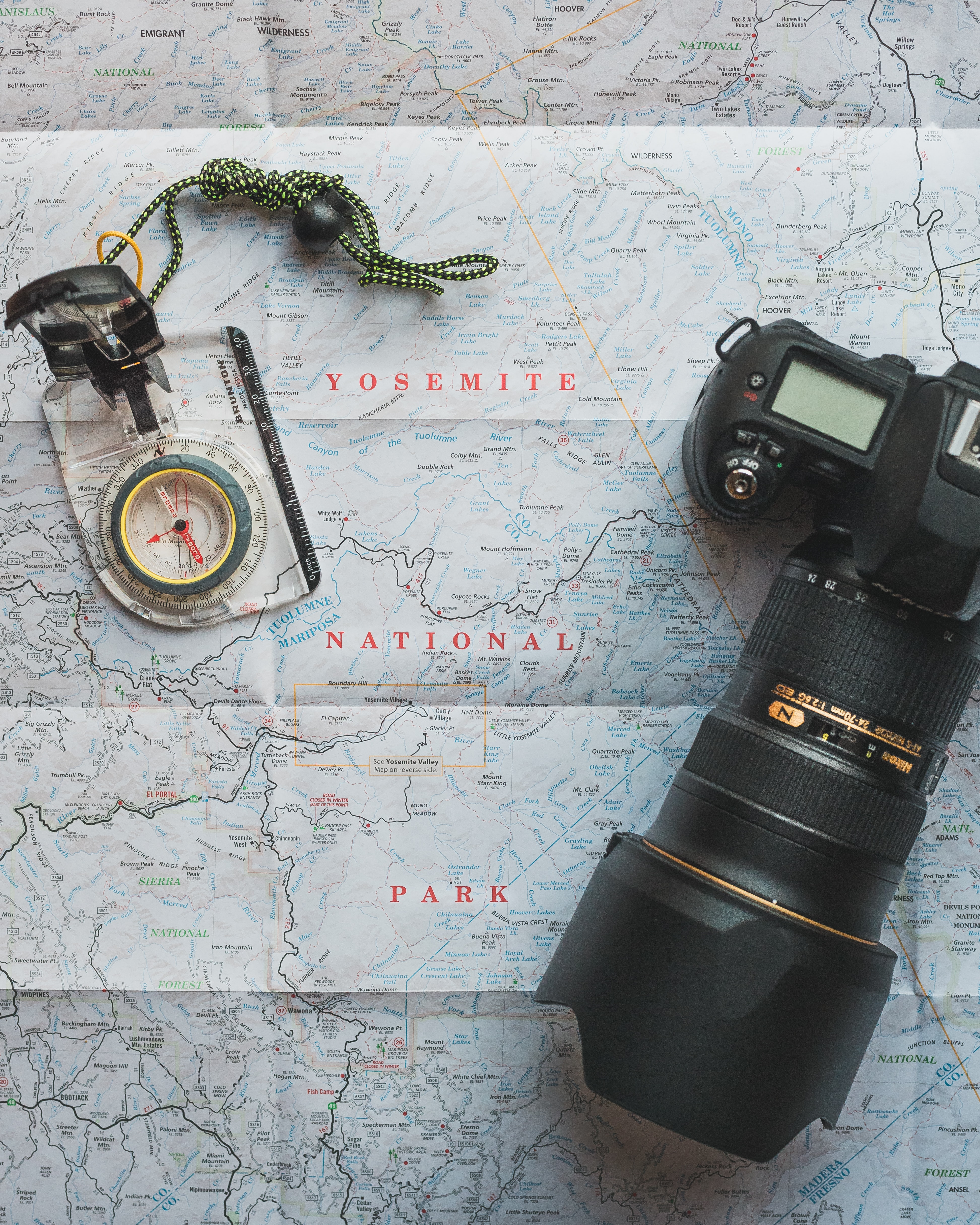 A camera with a telephoto lens and a compass laying on a map of Yosemite Valley