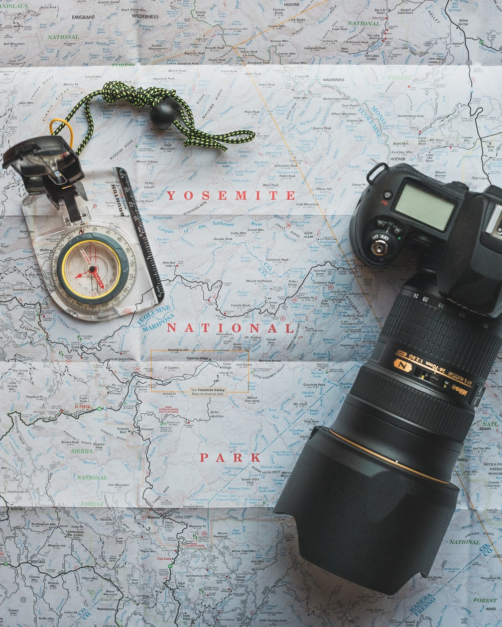 black Nikon DSLR camera beside of map compass