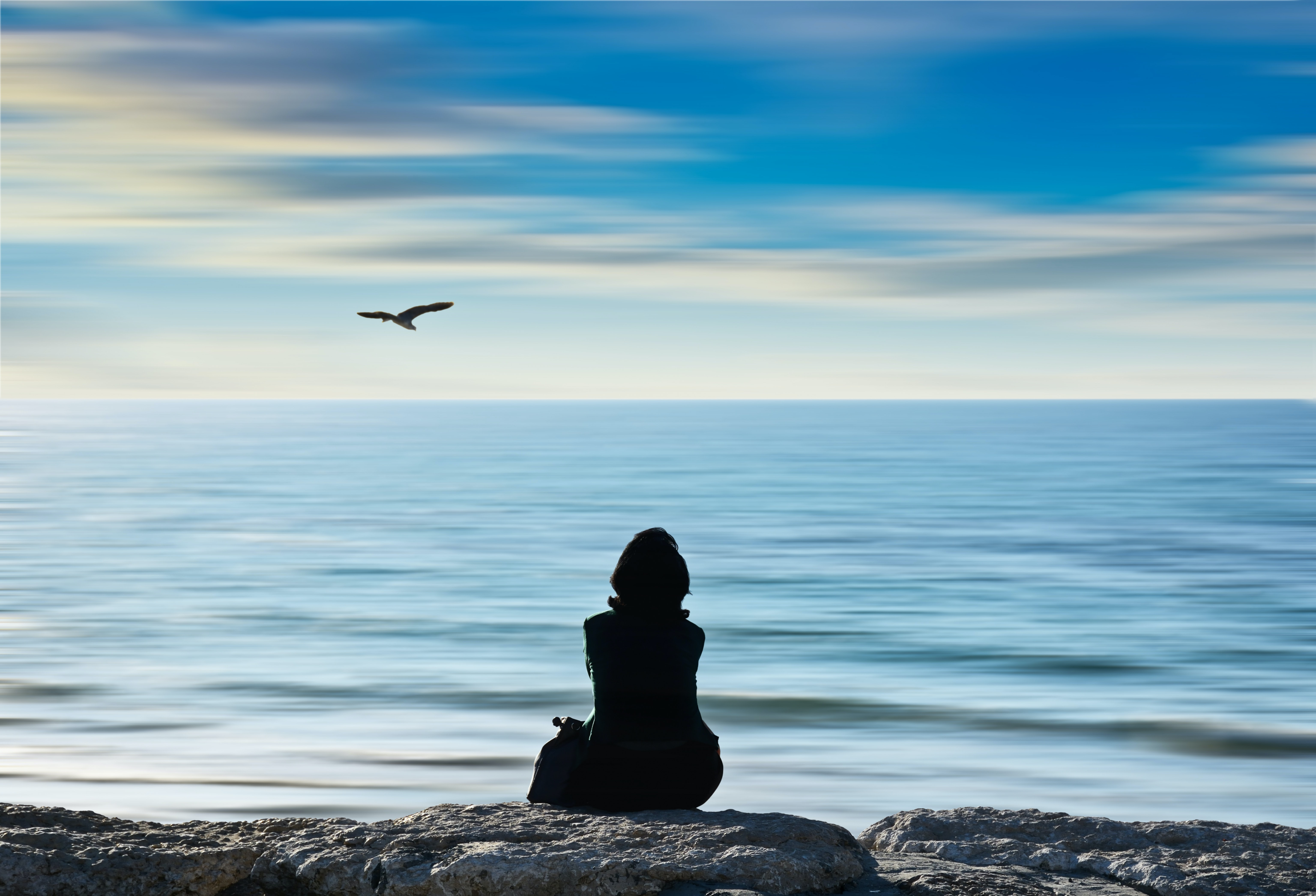 silhouette photo of person sitting on rock at the seashore