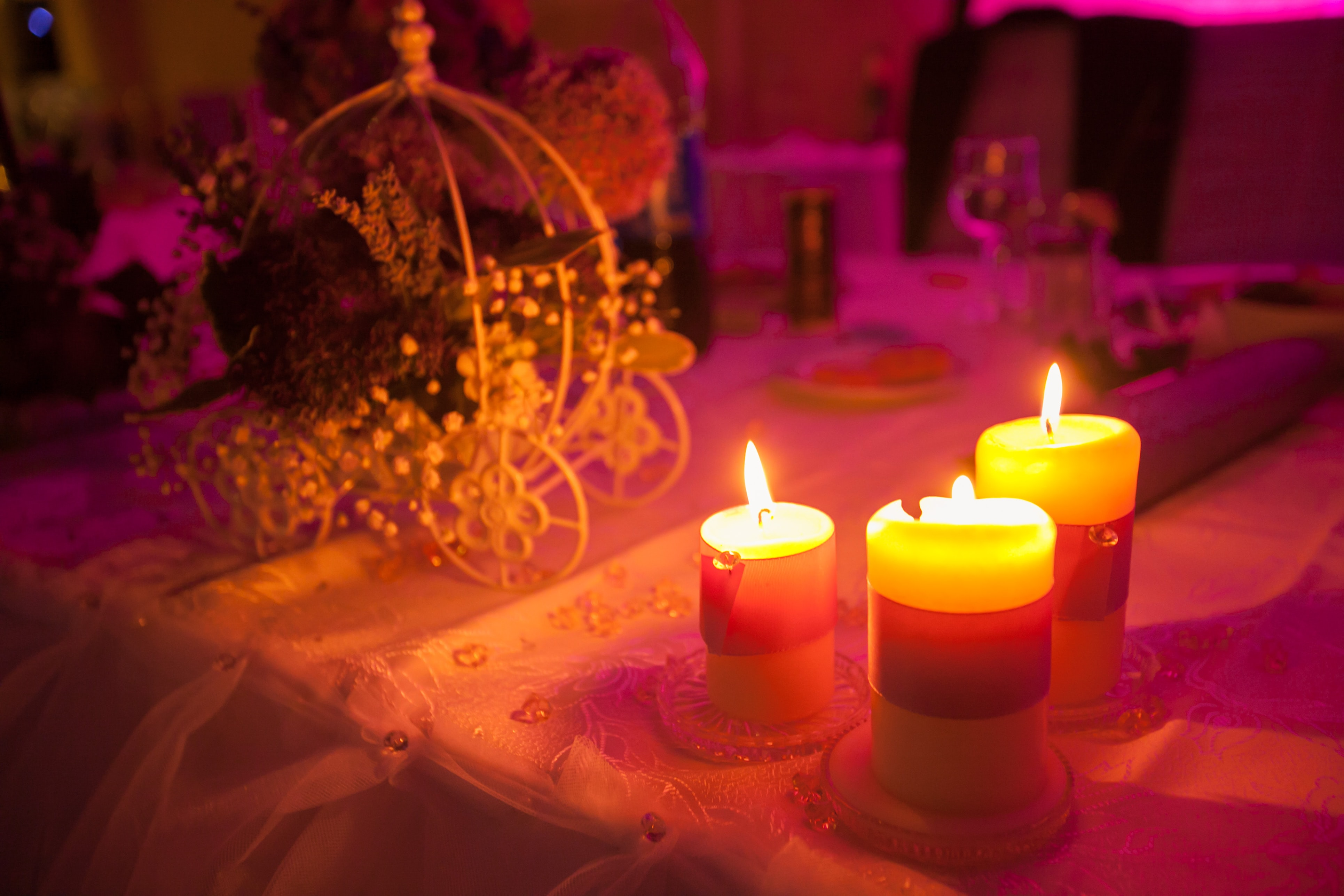 Three lit candles on a table at a princess themed party.